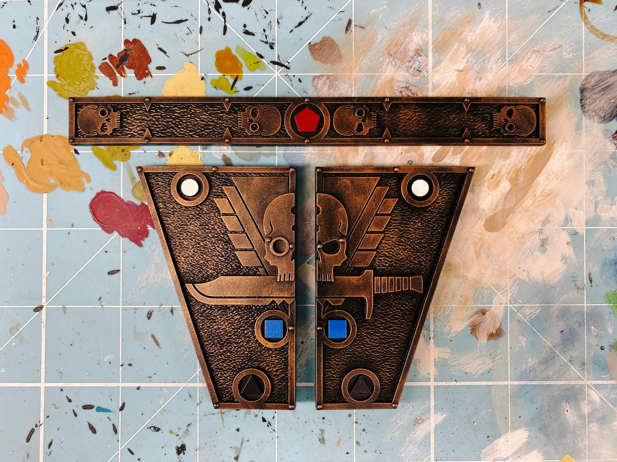 A photo of the three measuring gauges from Warhammer 40,000: Kill Team. One is long and thin with stylised skulls and a red pentagon. The other two are two halves of an isosceles trapezoid with a white circle, blue square, and black triangle on three of their edges, and half of a large skull with a knife under it on either side. They're all painted to look like worn brass.