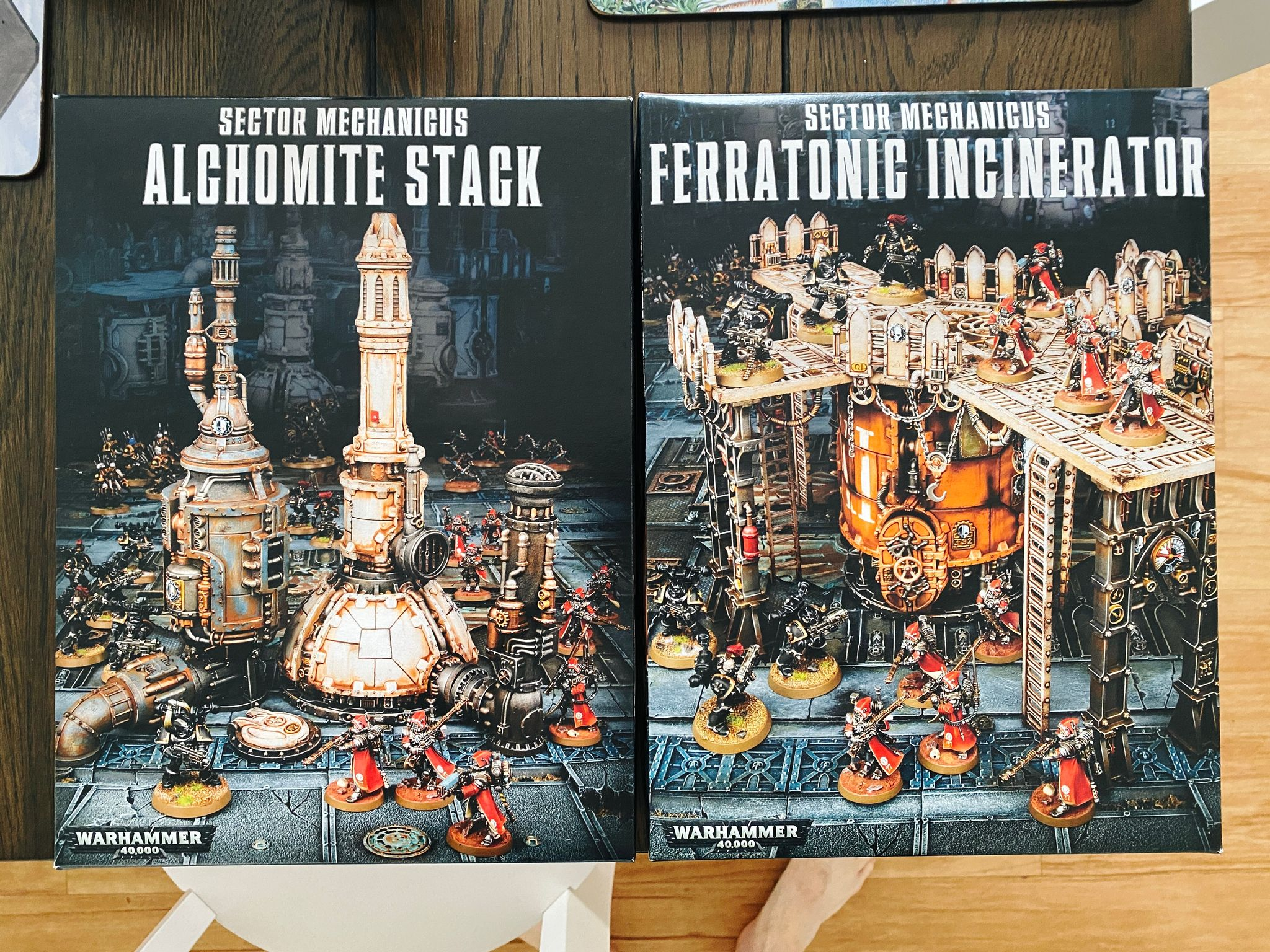 "A photo of two boxes of Warhammer 40,000 terrain, the ""Alchomite Stack"" and ""Ferratonic Incinerator"". It's extremely industrial-looking, borderline steampunk."