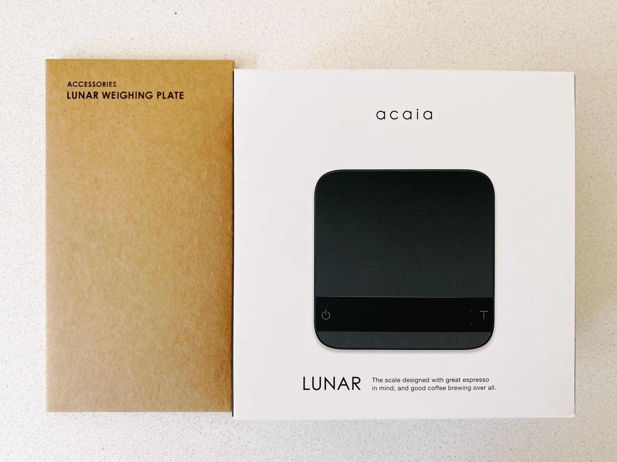 A photo of the box of a set of Acacia Lunar scales, and the additional magnetised plate to make it a little wider if you need it. The scales are ~10cm x 10cm square, with rounded corners, and thin enough to fit under your cup when you're making espresso.