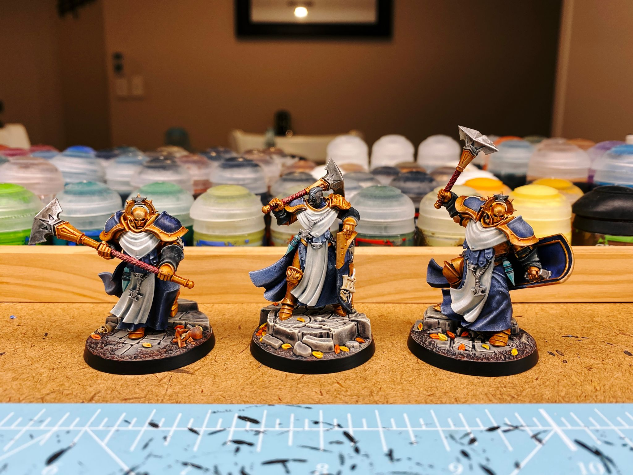 A photo of the three miniatures from the Warhammer Underworlds warband Ironsoul's Condemnors. They're armoured in heavy-looking gold armour with flowing blue robes, one's brandishing a huge hammer, another has a mace above his head mid-strike, and the third has her mace over her shoulder. The bases look like stone and have autumn leaves blowing around on them.