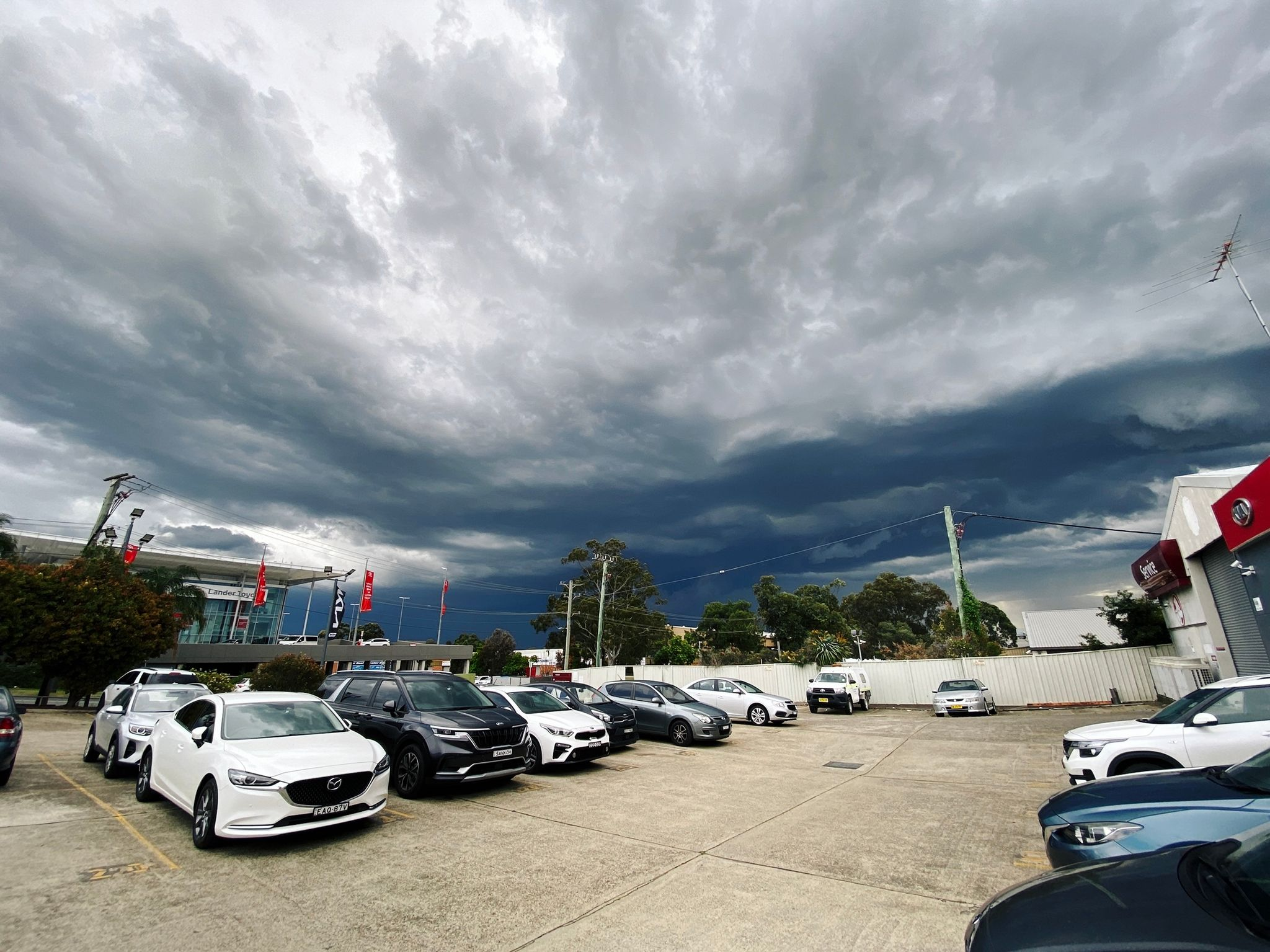A photo looking out over the parking lot of a car dealership. There's a VERY LARGE, VERY ANGRY bank of extremely dark clouds in the sky.