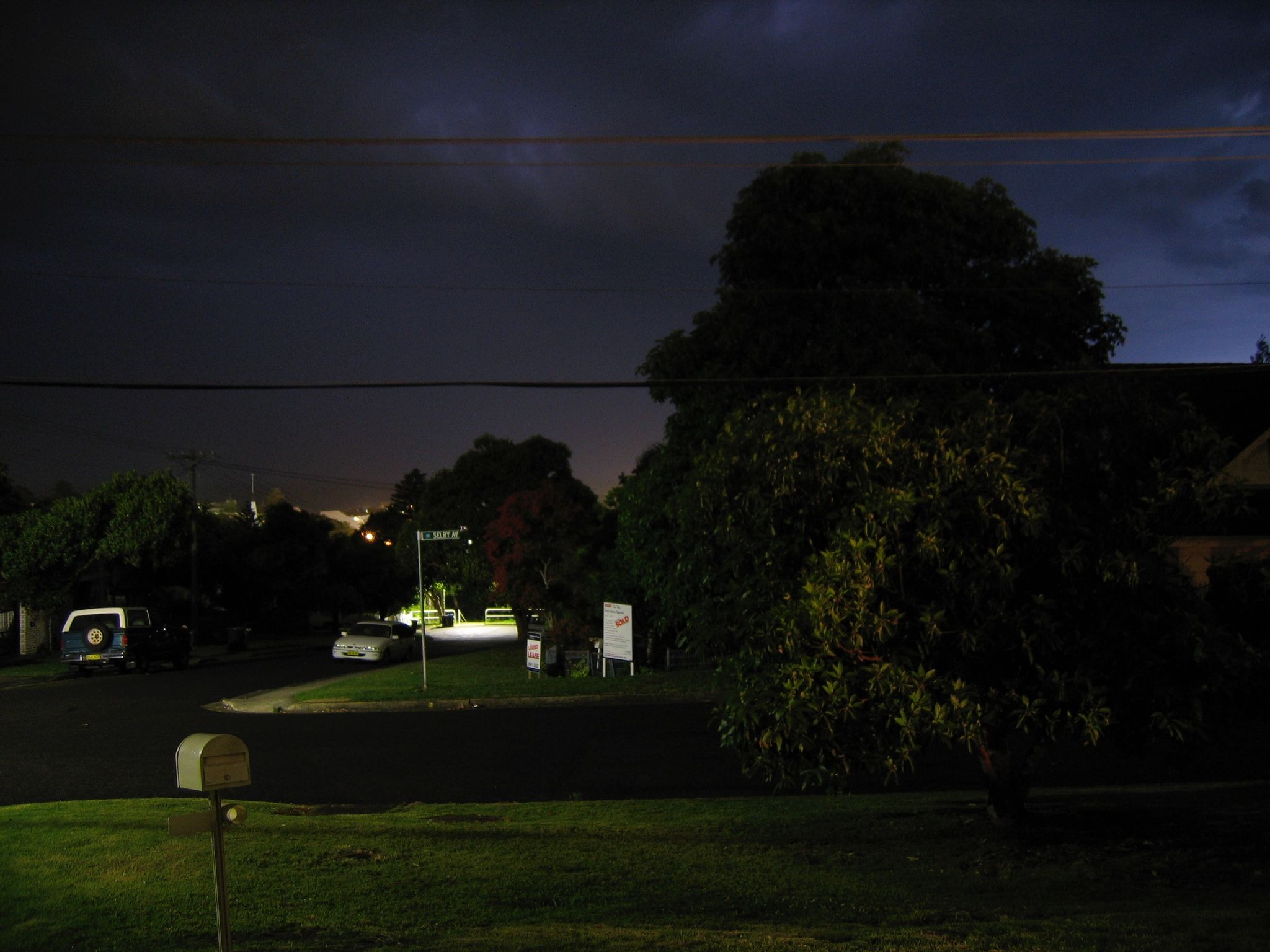A long-exposure nighttime photo looking at the street corner again, with distant lights visible over the trees at the left, and the clouds at the right being lit up from lightning.