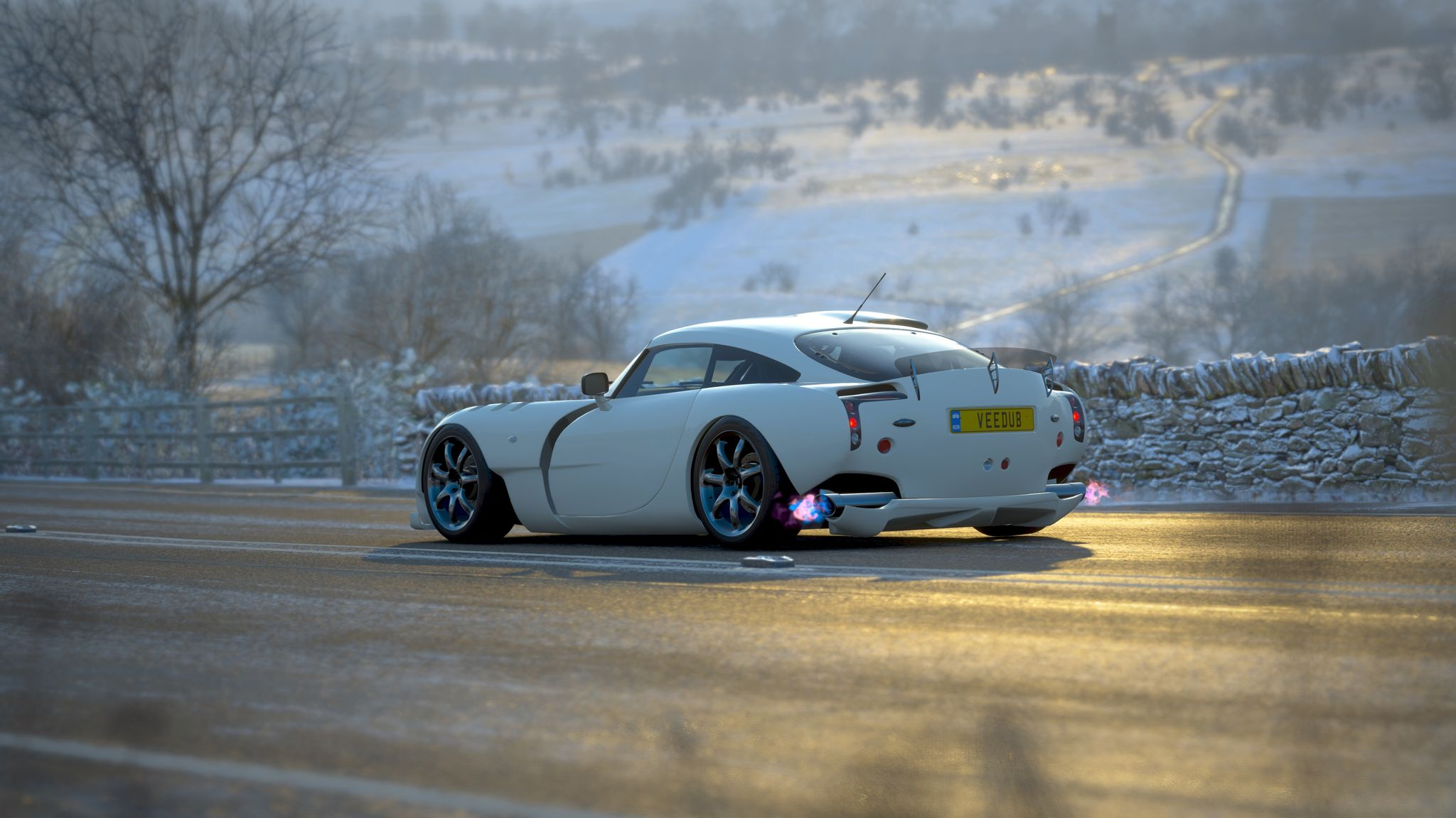 A screenshot (that looks more like a photo) of the rear 3/4 profile of a white TVR Sagaris driving down a road with snowy hills in the background. There's fire coming out of the exhaust pipes.