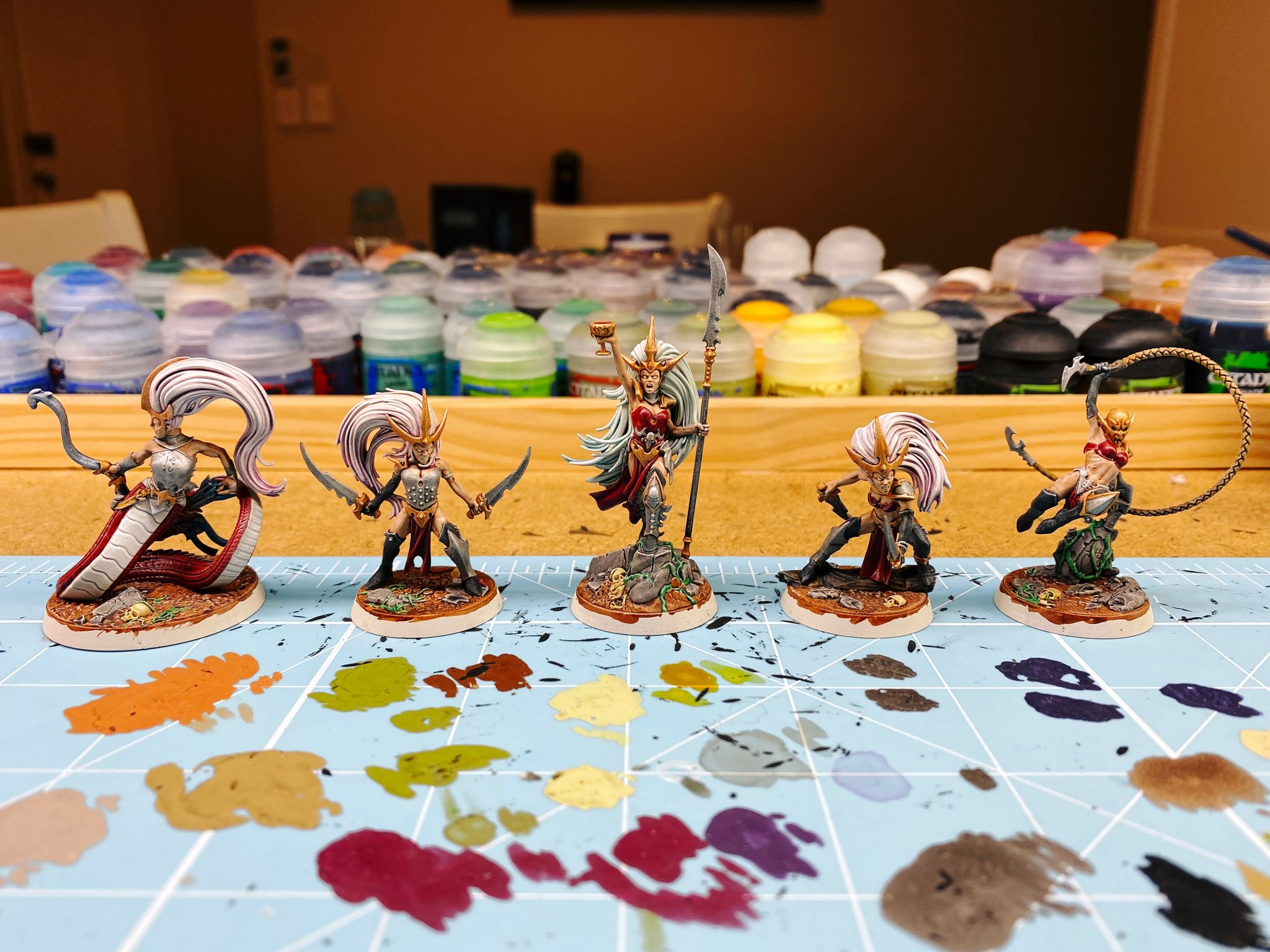 A photo of the warband Morgwaeth's Blade-coven from Warhammer Underworlds. Five female aelf miniatures, the one in the middle is holding a spear with a goblet raised in triumph and has long pale blue hair. The two on either side of her have long pale pink hair and are both holding swords like they're about to use them. The one on the left's bottom half of body is a snake and she's holding a bow. The right one has a whip and is mid-leap over a broken statue. They're all not wearing much armour.