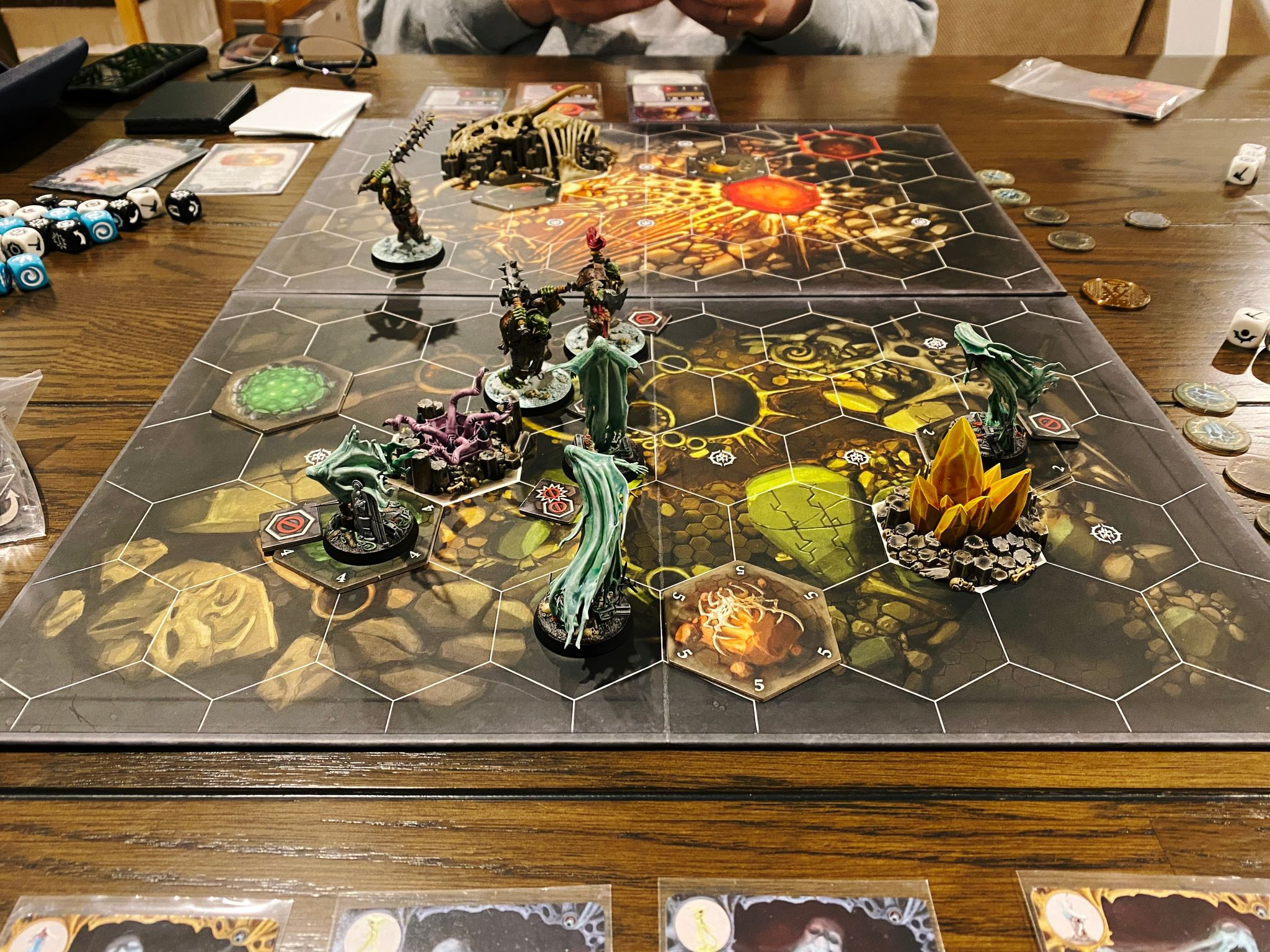 A photo of a Warhammer Underworlds board, with tiled hexes on it. Lady Harrow's Mournflight are at the front, consisting of four flowing ghostly-looking spirits. Facing them are Morgok's Krushas, three heavily armed and armoured orruks (orks).