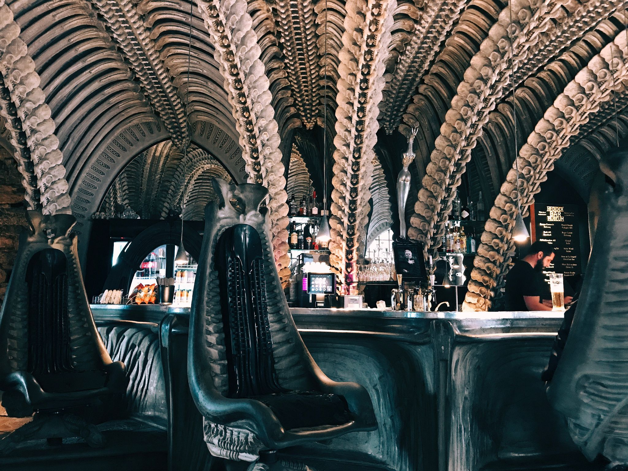 A photo of a bar, the walls look like they're made of spines and curve up and over. Two very high-backed chairs are in front of the bar and they also look like they're made from interlocking bones.