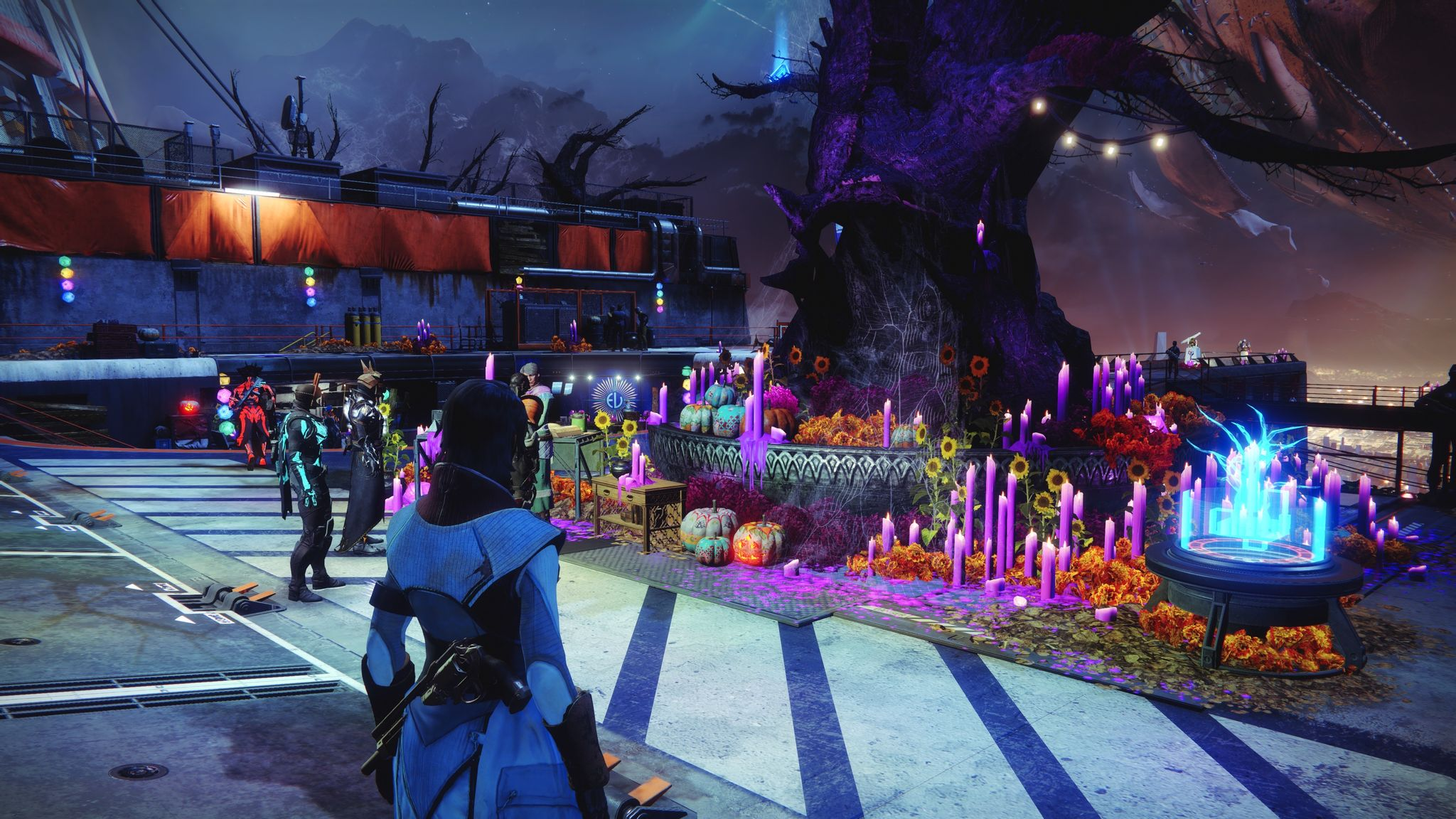 A screenshot from Destiny 2 showing a big gnarled tree in the middle of the Tower social space with lots of tall purple candles around the base of it. There's some pumpkins visible and also glowing paper-looking lights in the shape of a dodecahedron (note: might not actually be one, but that general geometric shape).