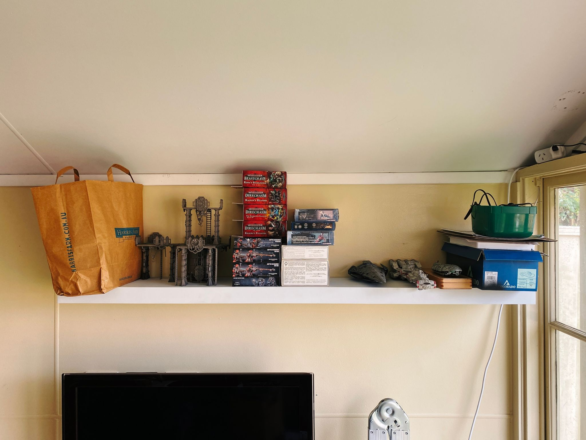 A photo of a white floating shelf with a bunch of boxes of Games Workshop miniatures in boxes, some of their plastic terrain, plus three large X-wing Miniatures Game miniatures.