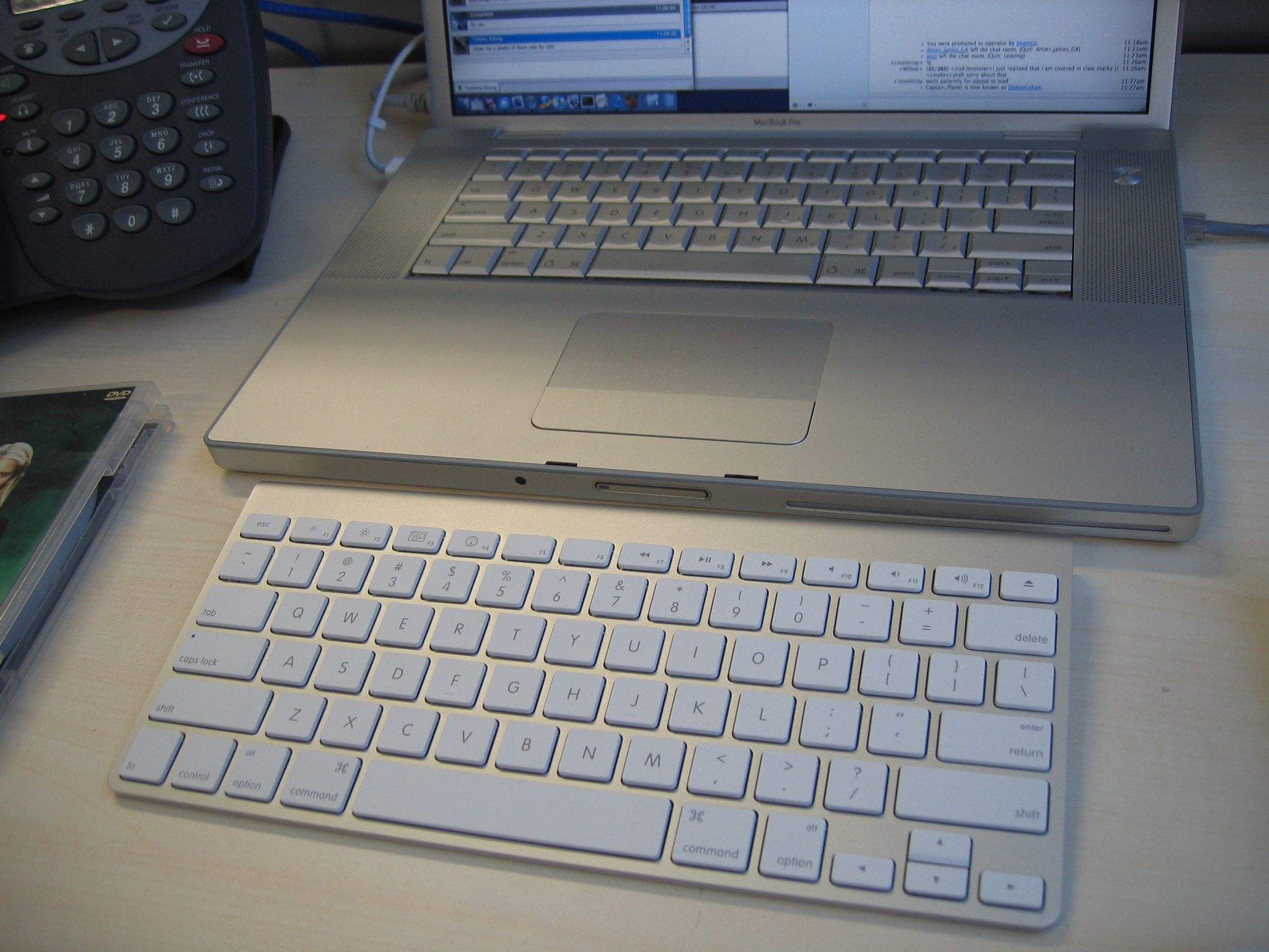 """A photo of an Apple Bluetooth """"chiclet""""-style keyboard sitting on a desk in front of a 15"""" MacBook Pro."""