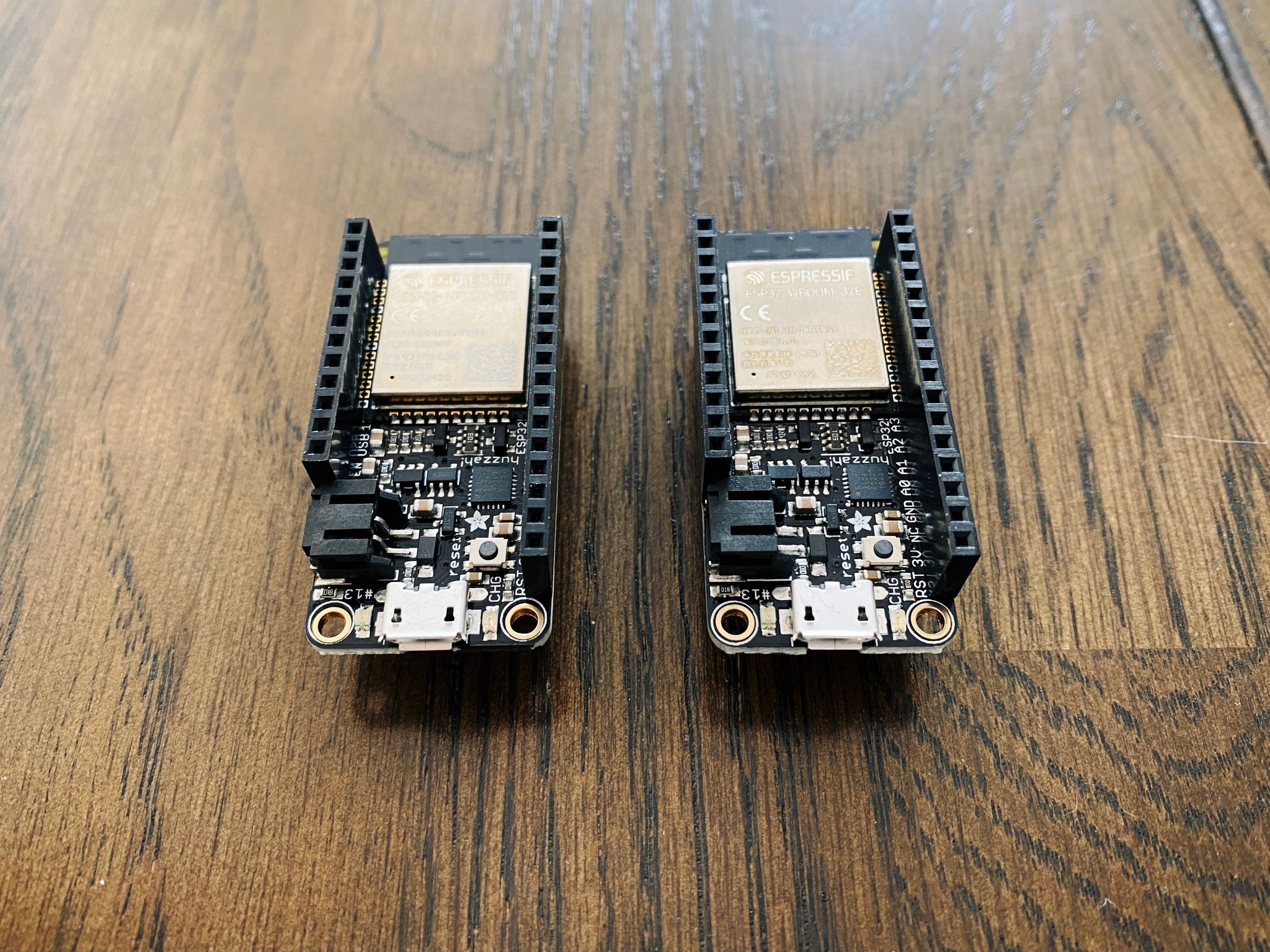 A photo of two very little rectangular circuit boards with various chips on them, and a row on either side of the boards with black plastic headers for plugging things into.