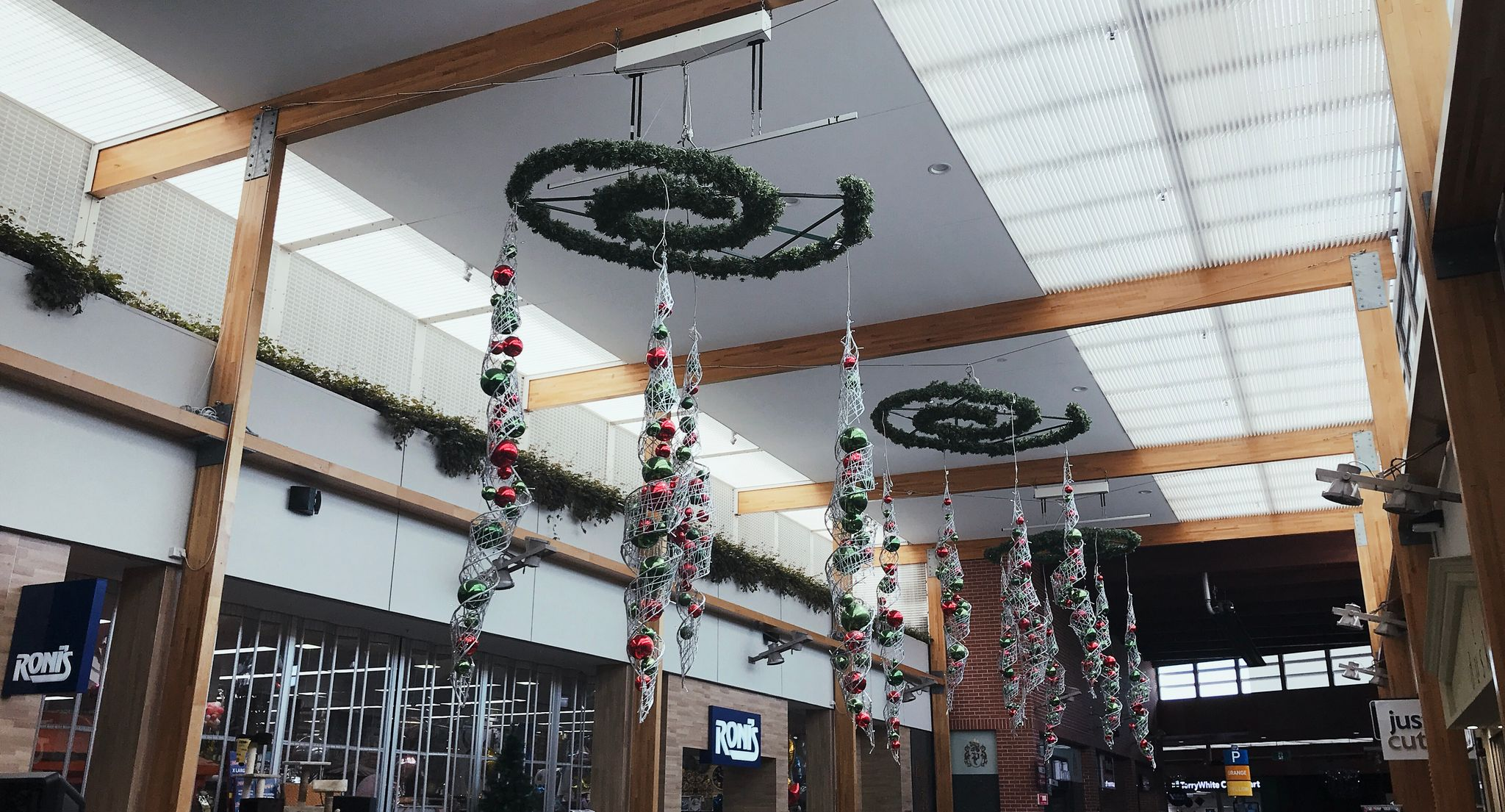A series of very large Christmas baubles hanging from a high ceiling in a mall.