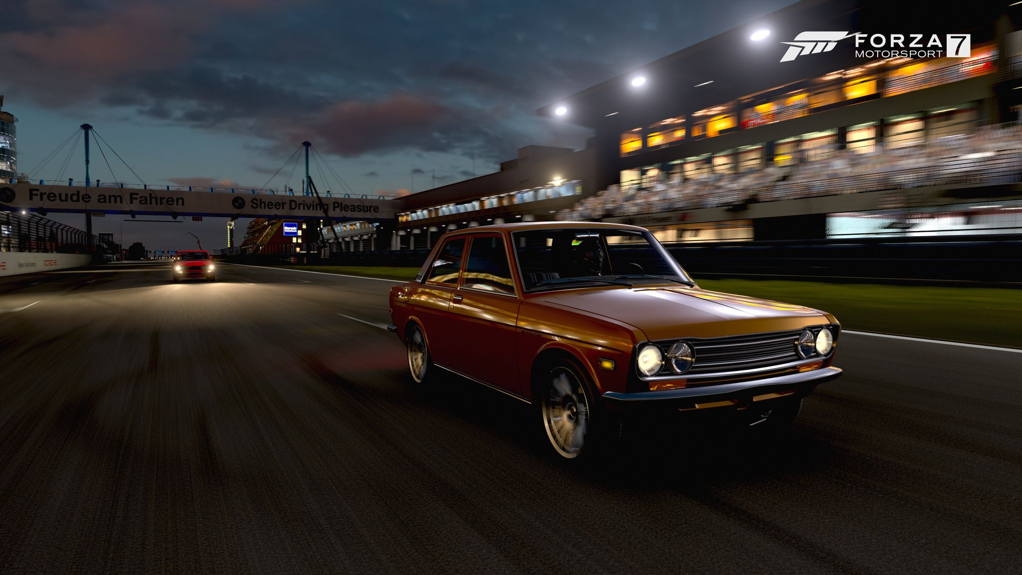 A screenshot from Forza Motorsport 7 showing a Datsun 510 at night zooming down the finishing straight at the Nurburgring GP circuit.