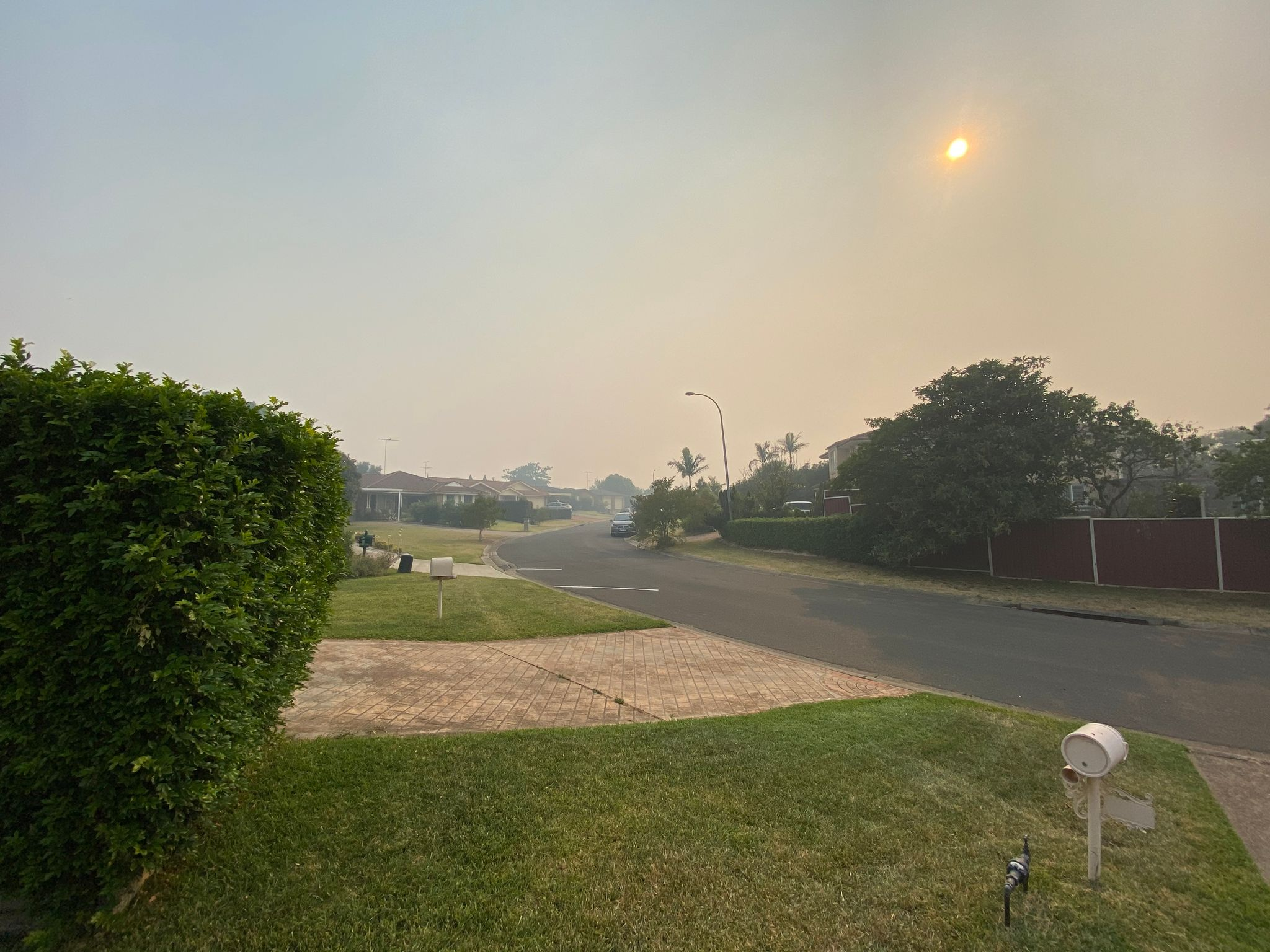 A photo of a suburban street, everything is brown-tinged due to bushfire smoke in the air.