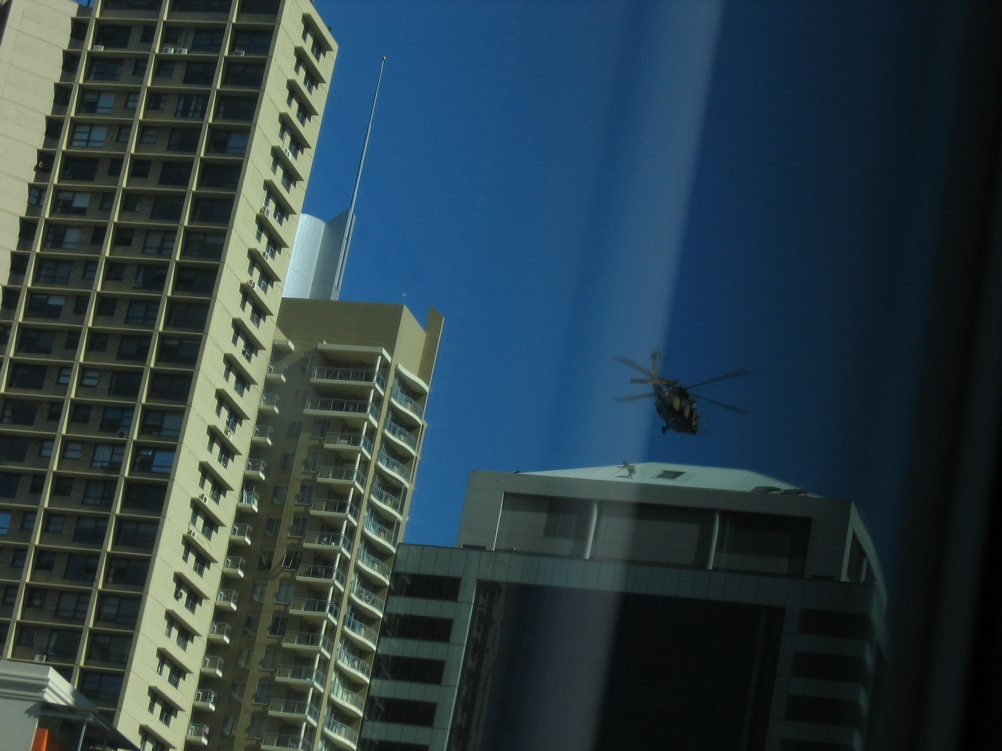 A photo of a Blackhawk helicopter hovering above a tall city building.