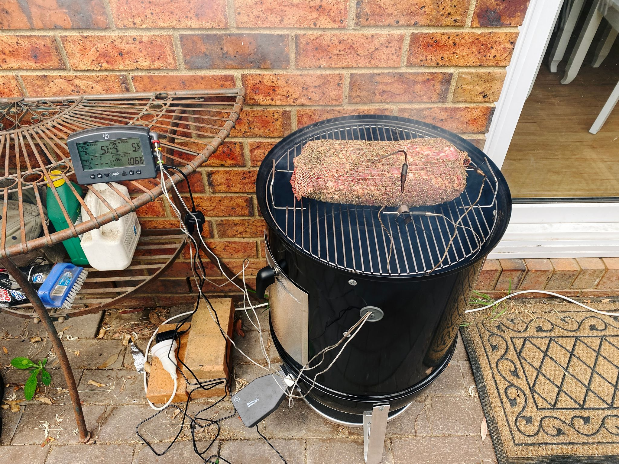 A photo of a big pork shoulder sitting on a Weber Smokey Mountain smoker, with a ThermoWorks temperature sensor on the table next to it and probes going into the meat and sitting alongside it to measure the ambient temperature in the smoker.
