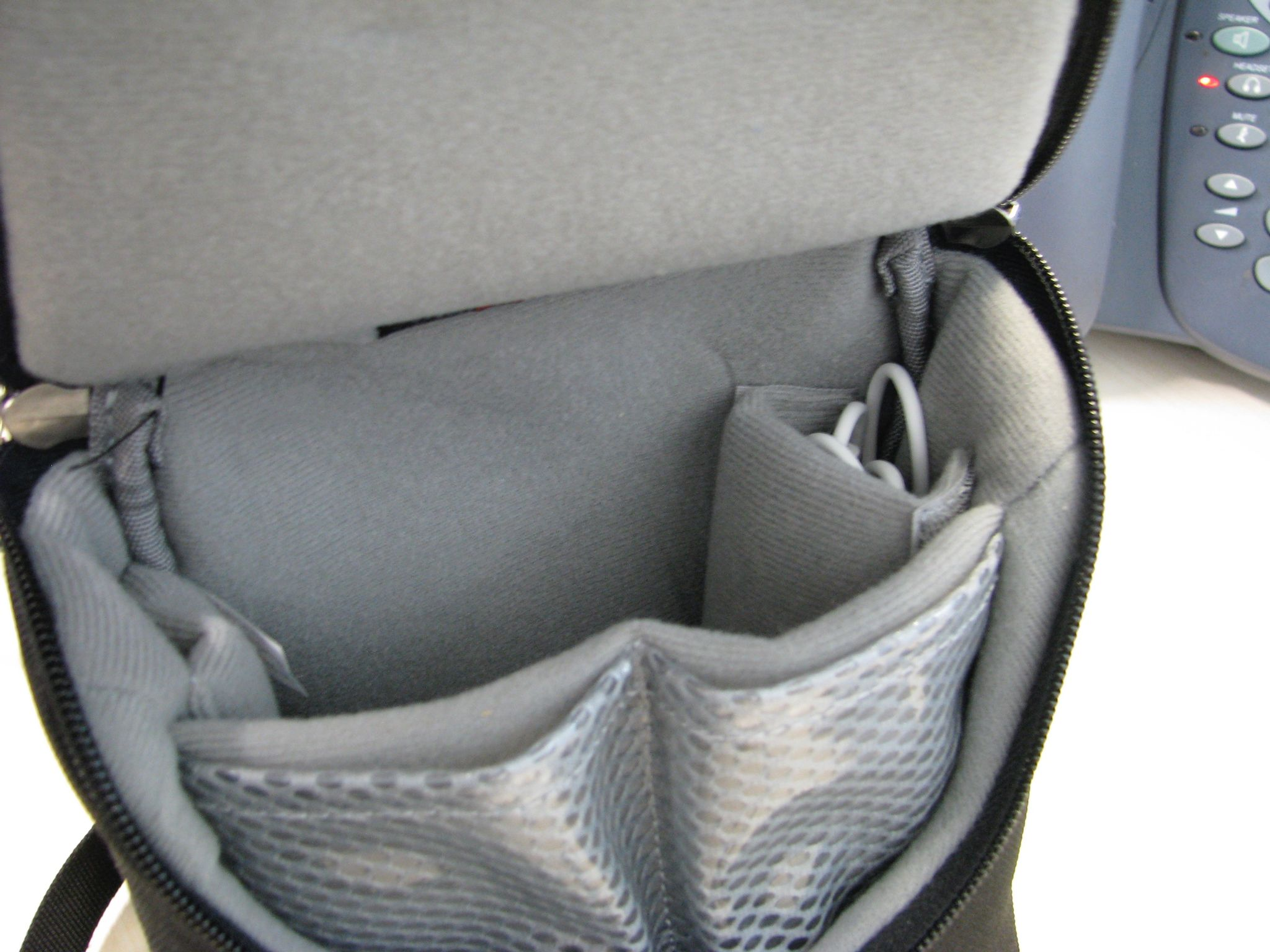 A photo of the inside of a small Lowepro brand shoulder-bag camera bag showing the compartments.
