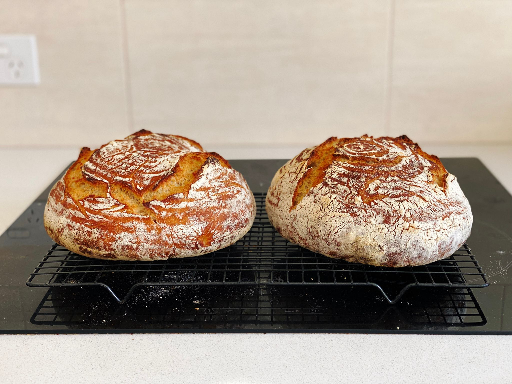 A photo of two round golden brown loaves of bread covered in flour sitting on a cooling rack.