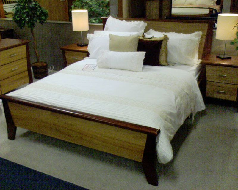 A photo of a queen-size bed in a shop. The frame is wooden, with a tall bedhead.