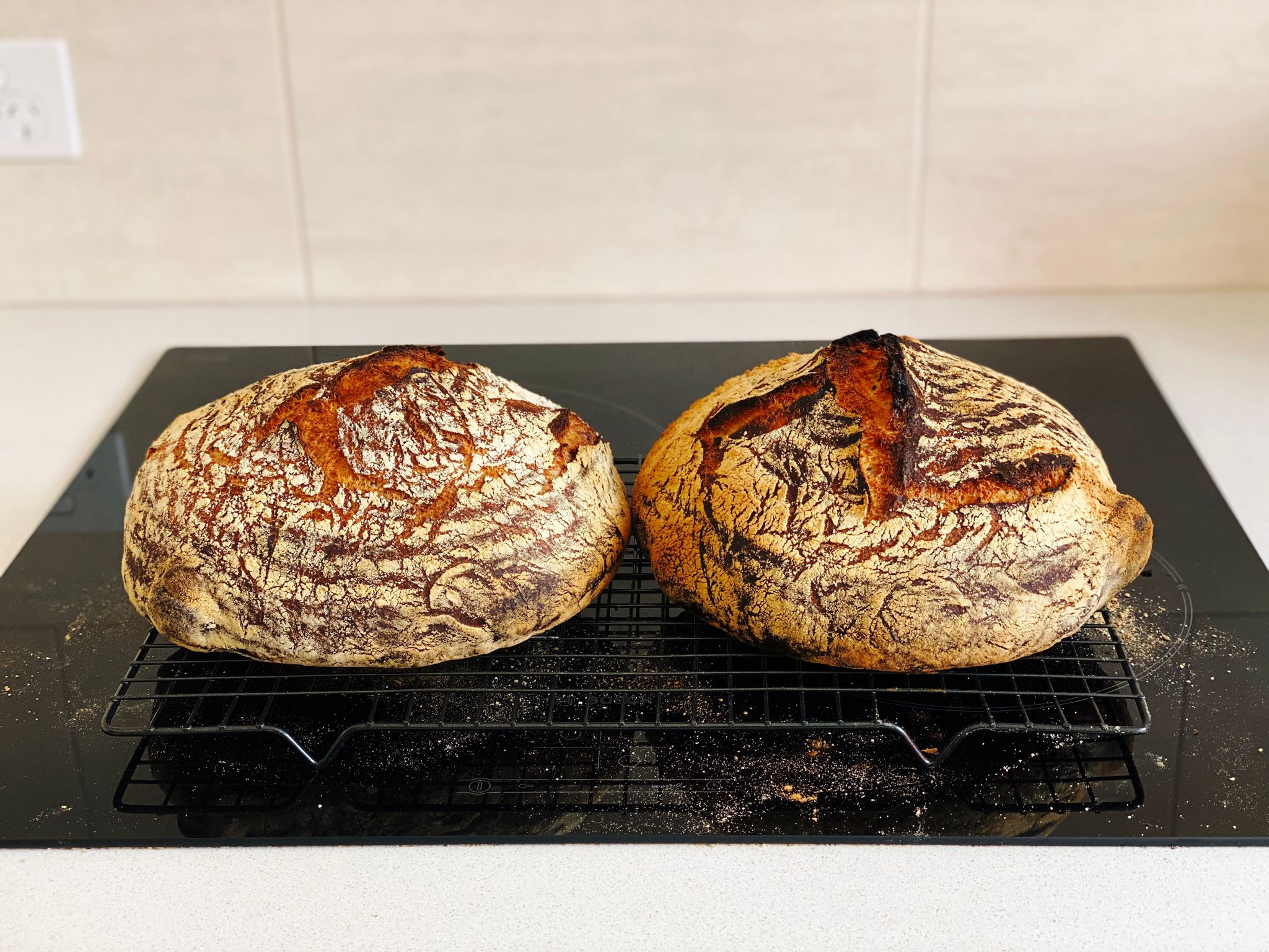 A photo of two round dark brown loaves of bread sitting on a cooling rack.