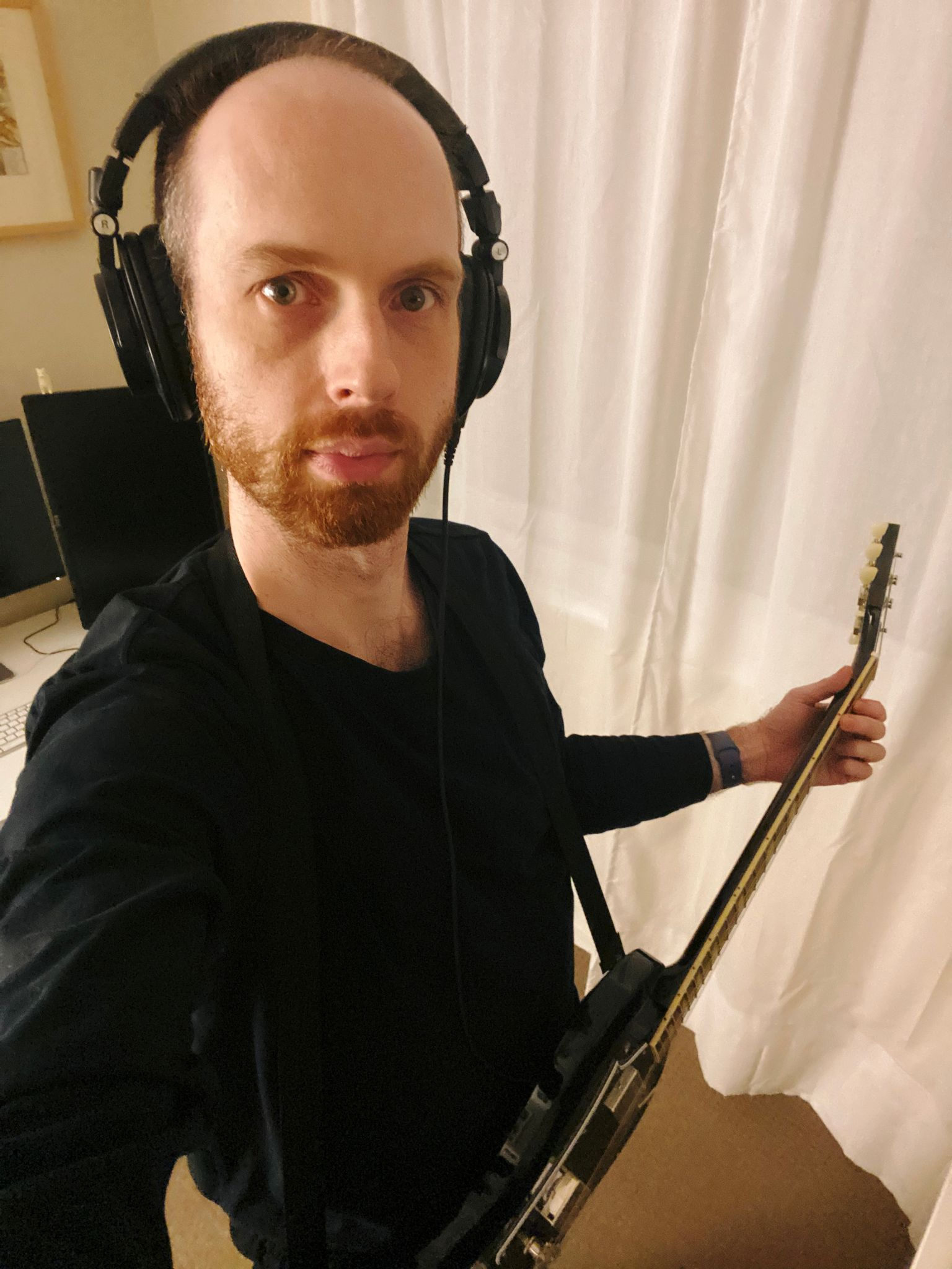 A selfie of me, a white man with a short red beard and short hair, standing with a black electric guitar and big headphones on.