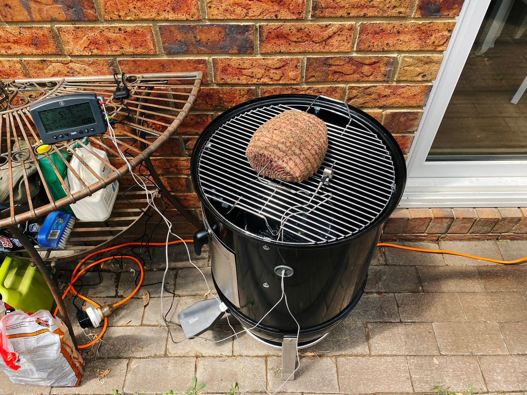 A photo of a pork shoulder sitting on the top grill of a Weber Smokey Mountain smoker.