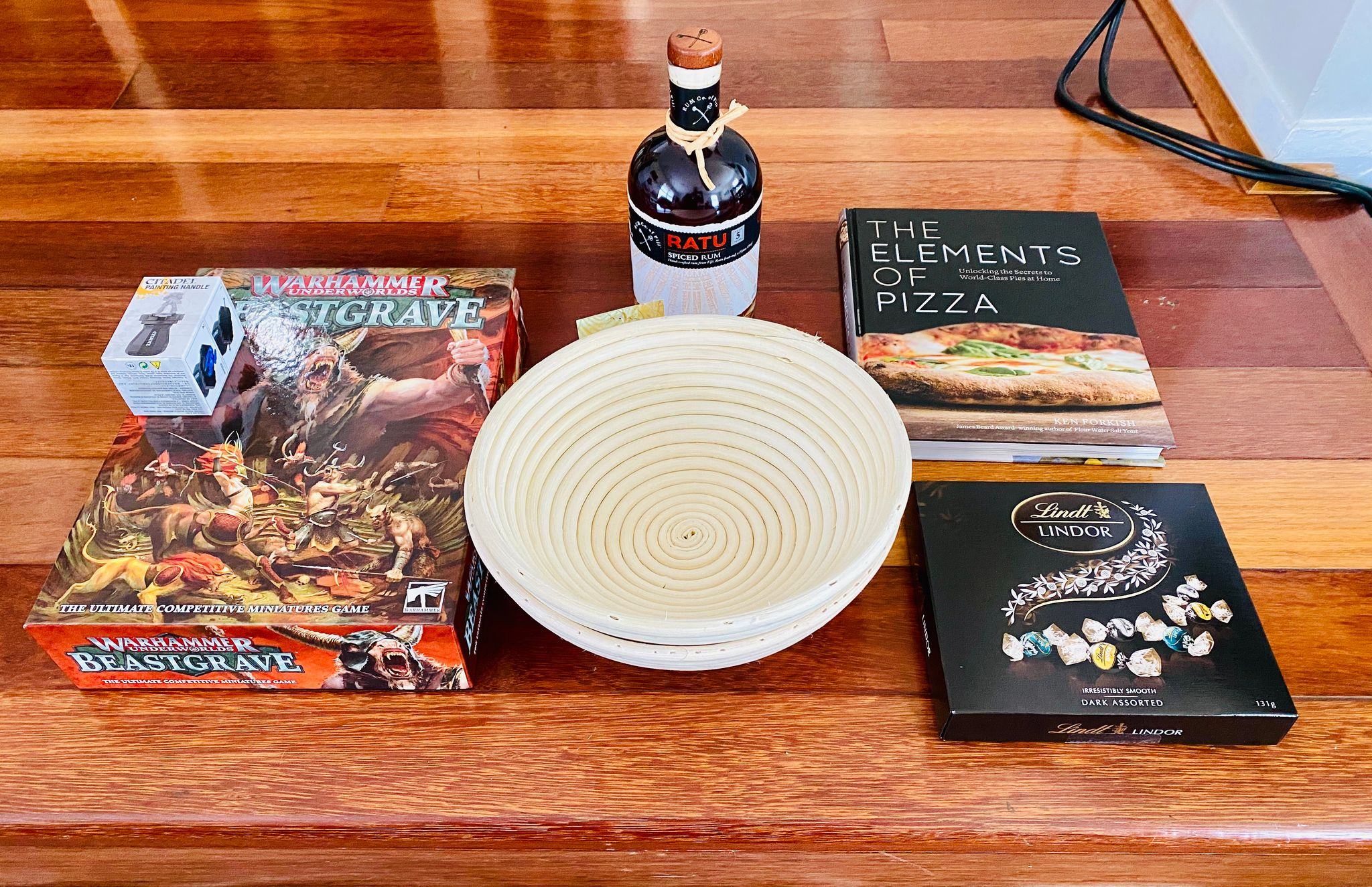 "A photo of Warhammer Underworlds: Beastgrave, two bread proofing baskets, a bottle of Fijian rum, a box of Lindt dark chocolate balls, and a book ""The Elements of Pizza""."