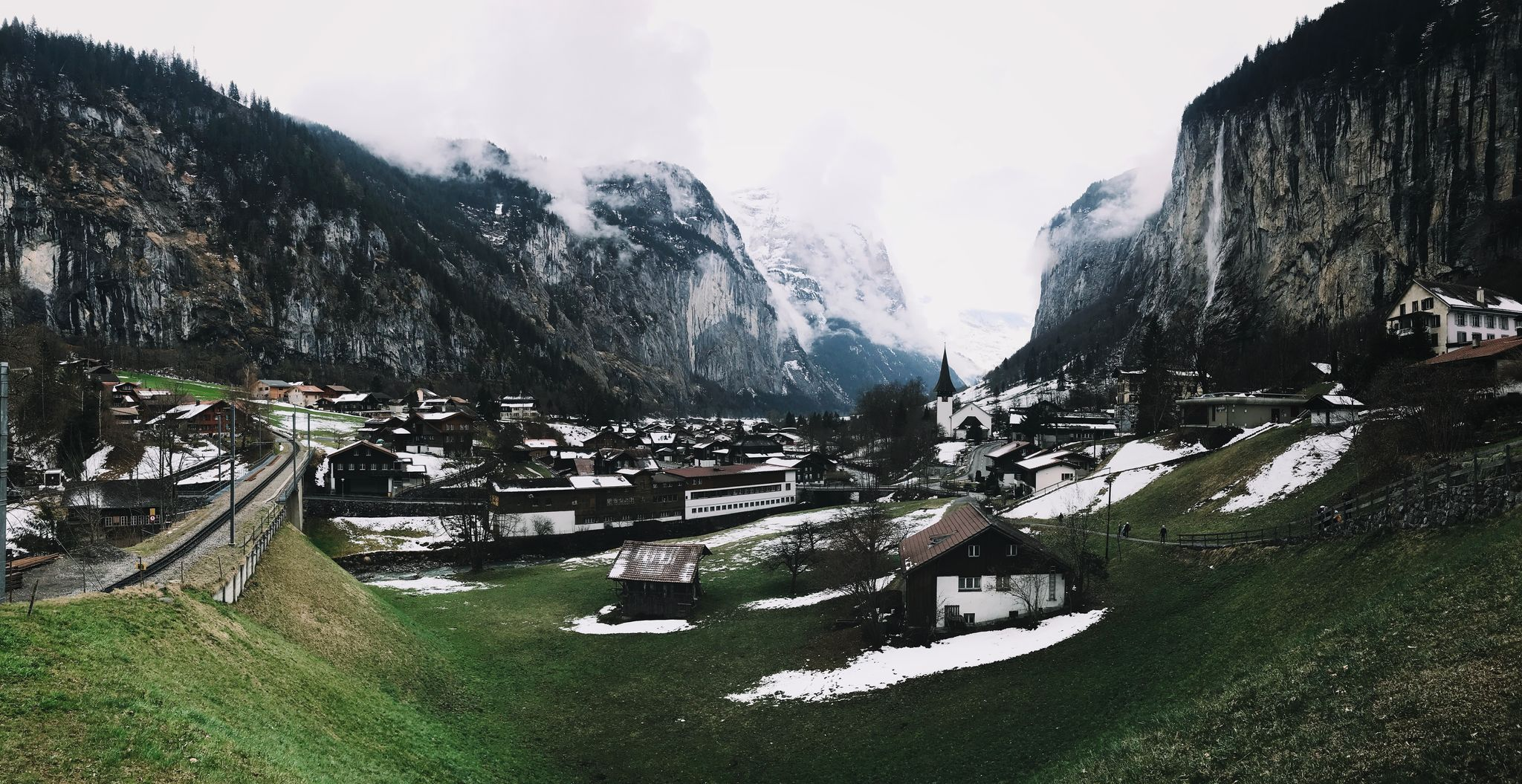 A view of a Swiss village on the hillside with very large craggy mountains in the background.
