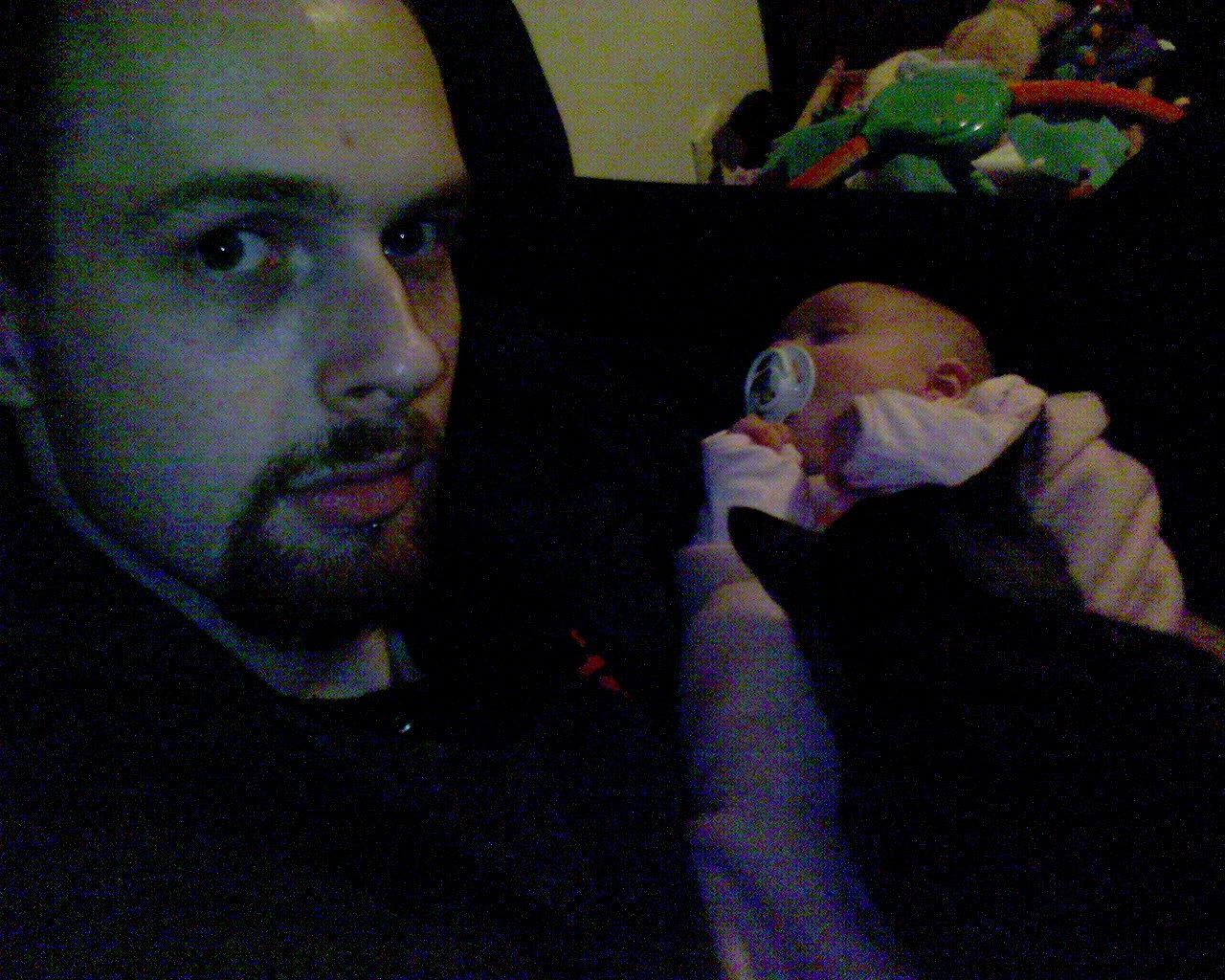 A very poor quality selfie of me, a white man with a goatee, with a sleeping baby in blankets on my lap, and a kitten on the blankets.