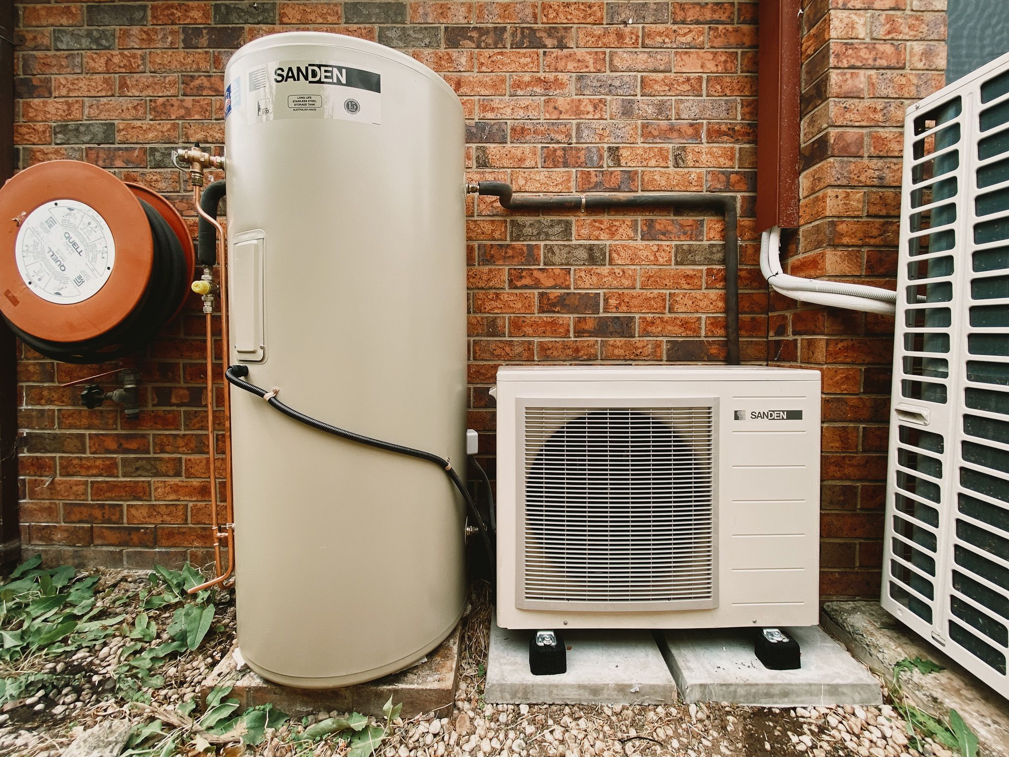 A photo of our heat pump hot water system, which is comprised of a standard-looking hot water water tank with what looks like a small air conditioning compressor next to it.