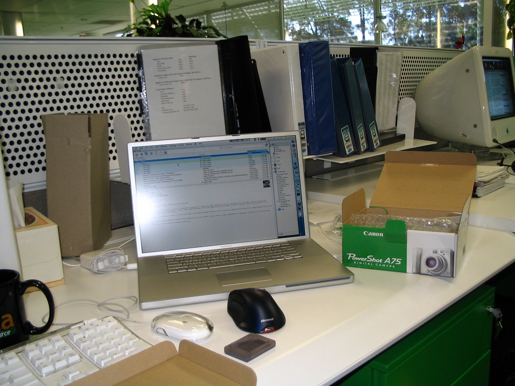 "A photo of a 17"" PowerBook G4 sitting on a desk alongside an opened box for a Canon PowerShot A75 camera (the camera that this photo was taken with)."