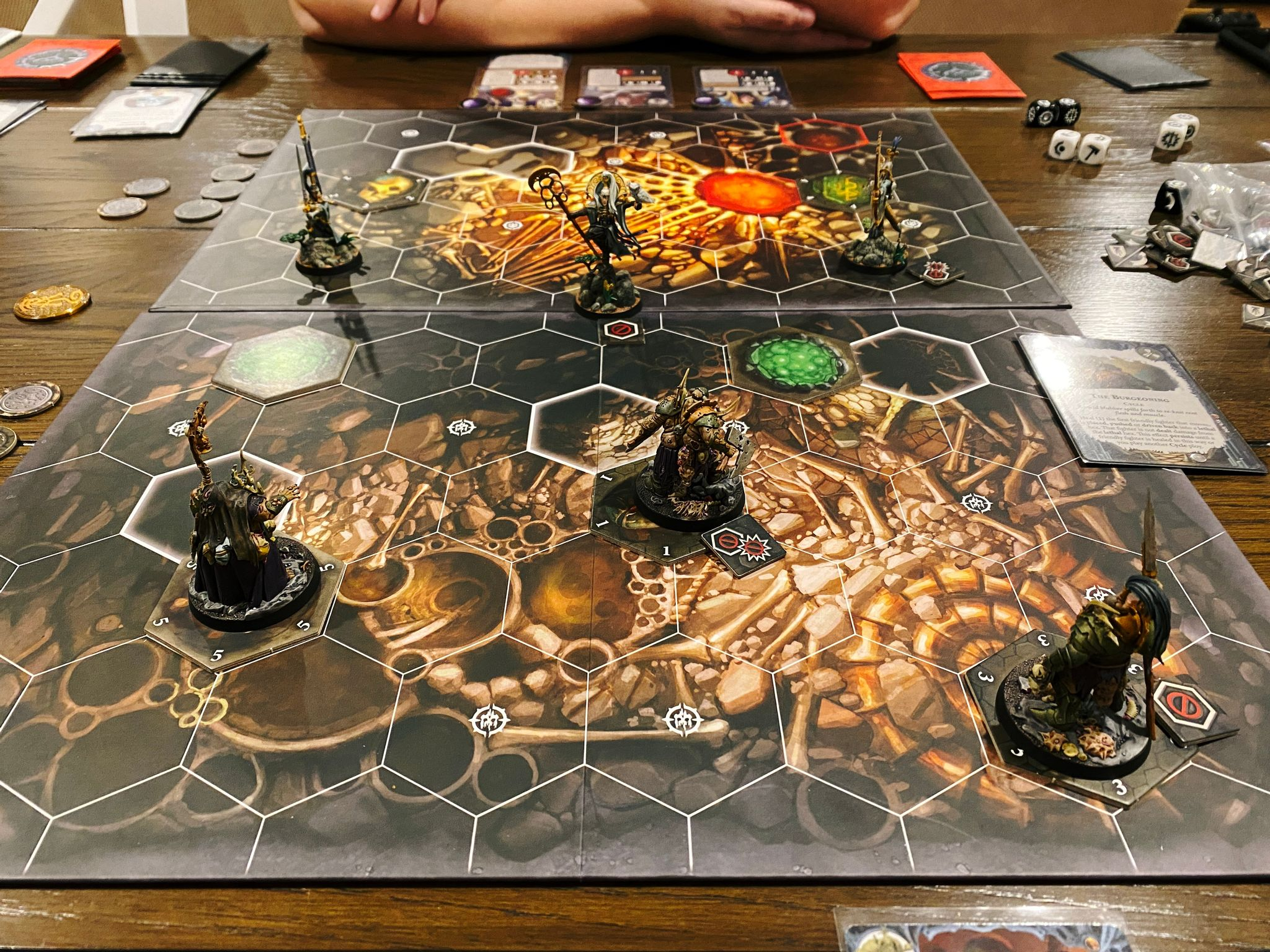 A photo of a Warhammer Underworlds game board. The board design is the inside of a cave and has hexagonal tiles on it. The three miniatures on my side of the table are bulky and slow-moving, and the three on Kristina's side are lithe and elegant aelves.