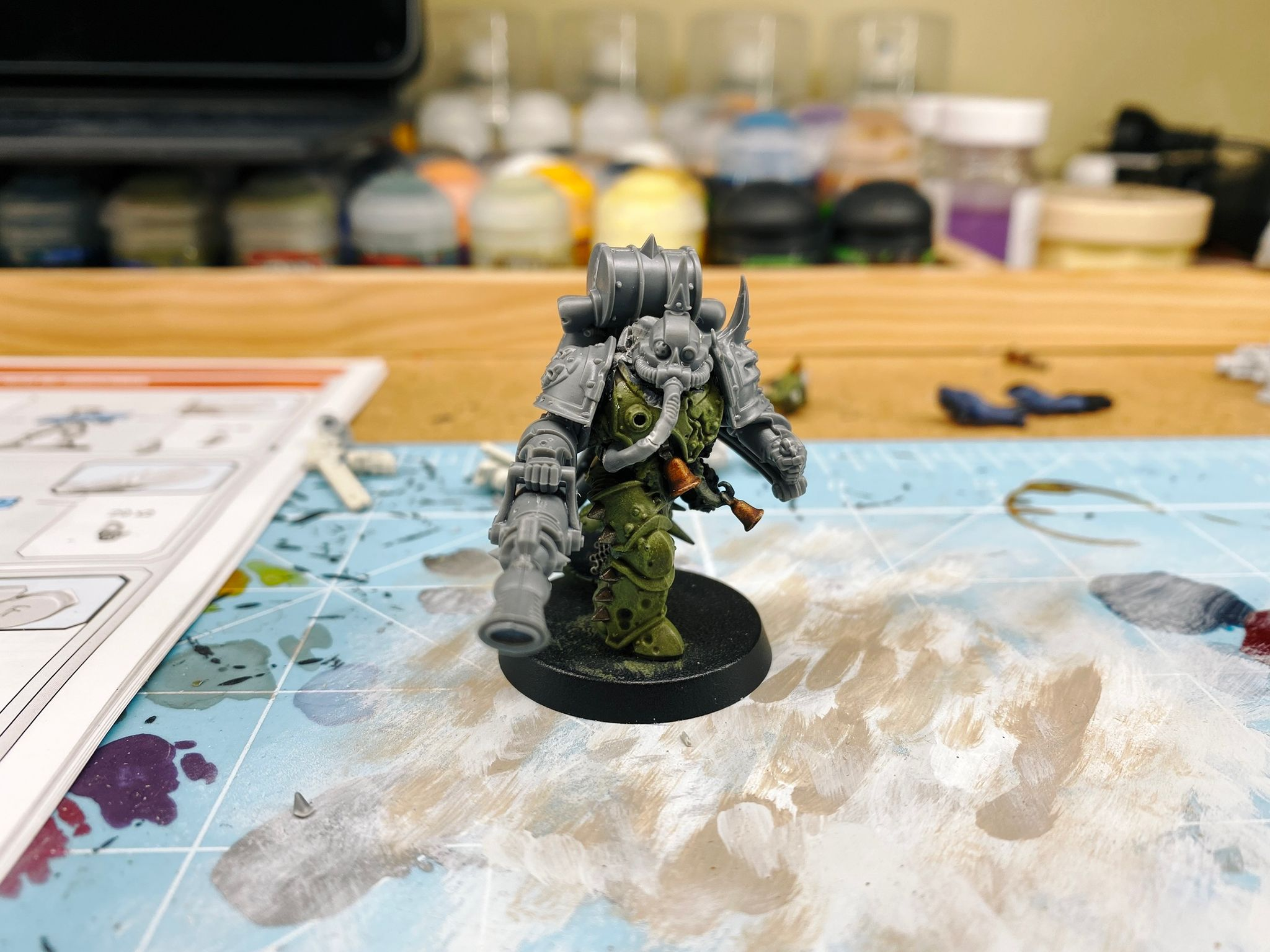 A photo of a Warhammer 40,000 Plague Marine, he has pock-marked heavy armour and spikes all over. He's in mid-stride and is holding a very large flamethrower-looking thing. His head, backpack, and both arms are unpainted bare plastic and are the new parts I added.