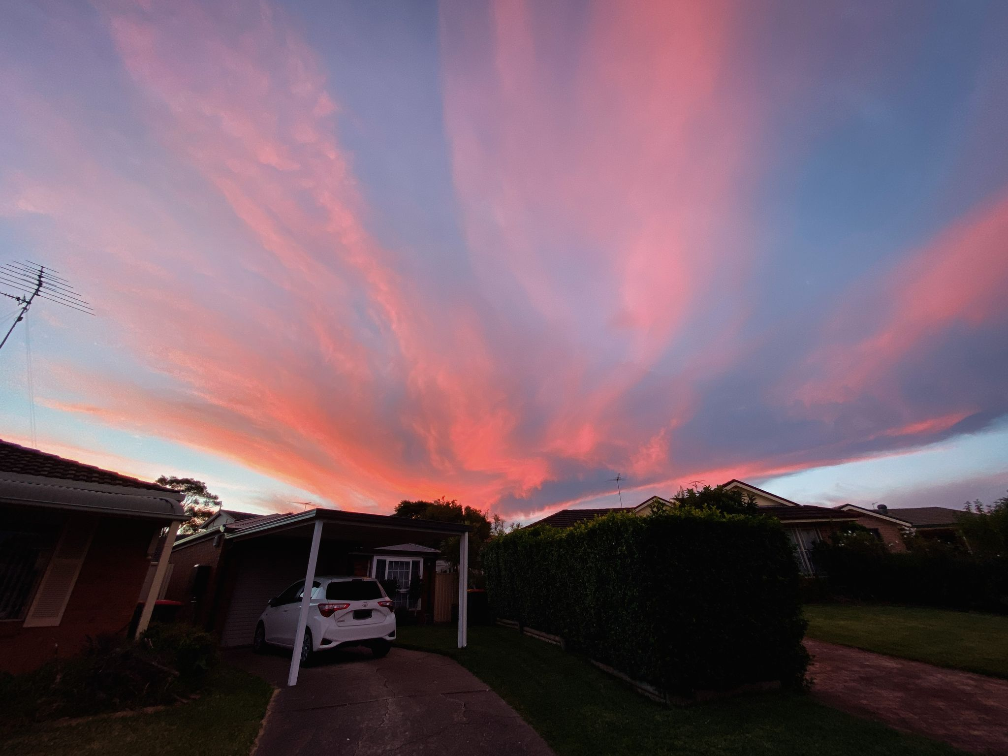 A photo looking out over our house from the front driveway, the clouds are all orange and pinky.