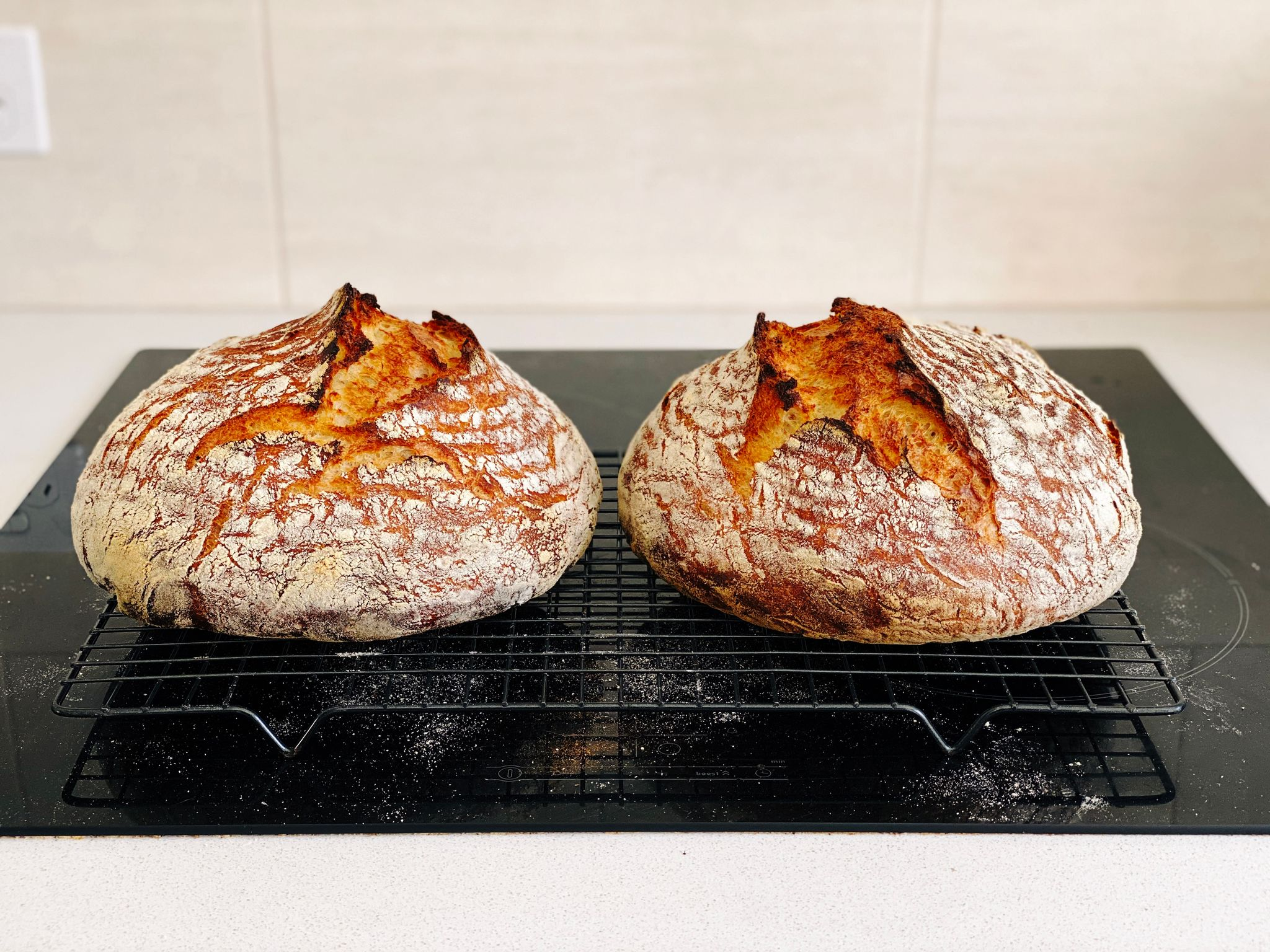 A photo of two golden brown loaves of bread sitting on a cooling rack.