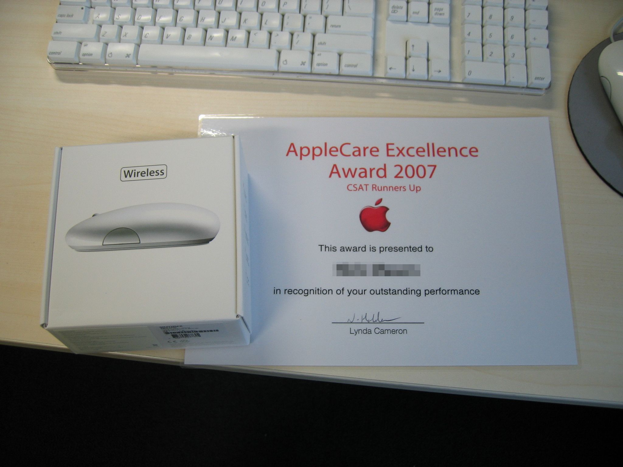 """A photo of the box of an Apple Wireless Mighty Mouse, alongside a certificate that says """"AppleCare Excellence Award 2007 - CSAT Runners Up""""."""