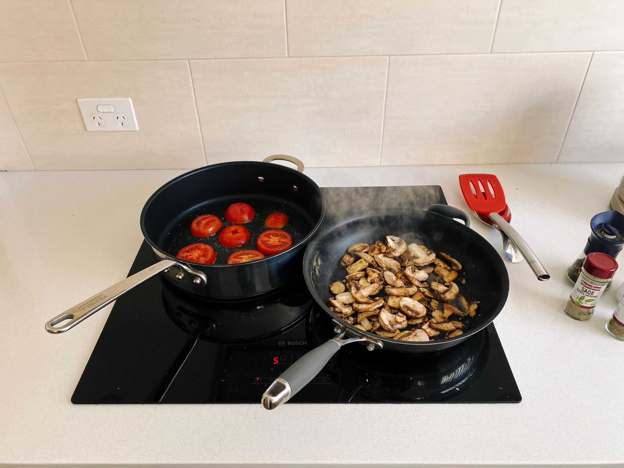 A photo of two frying pans on a stove, one with sliced tomatoes in it, the other with mushrooms.