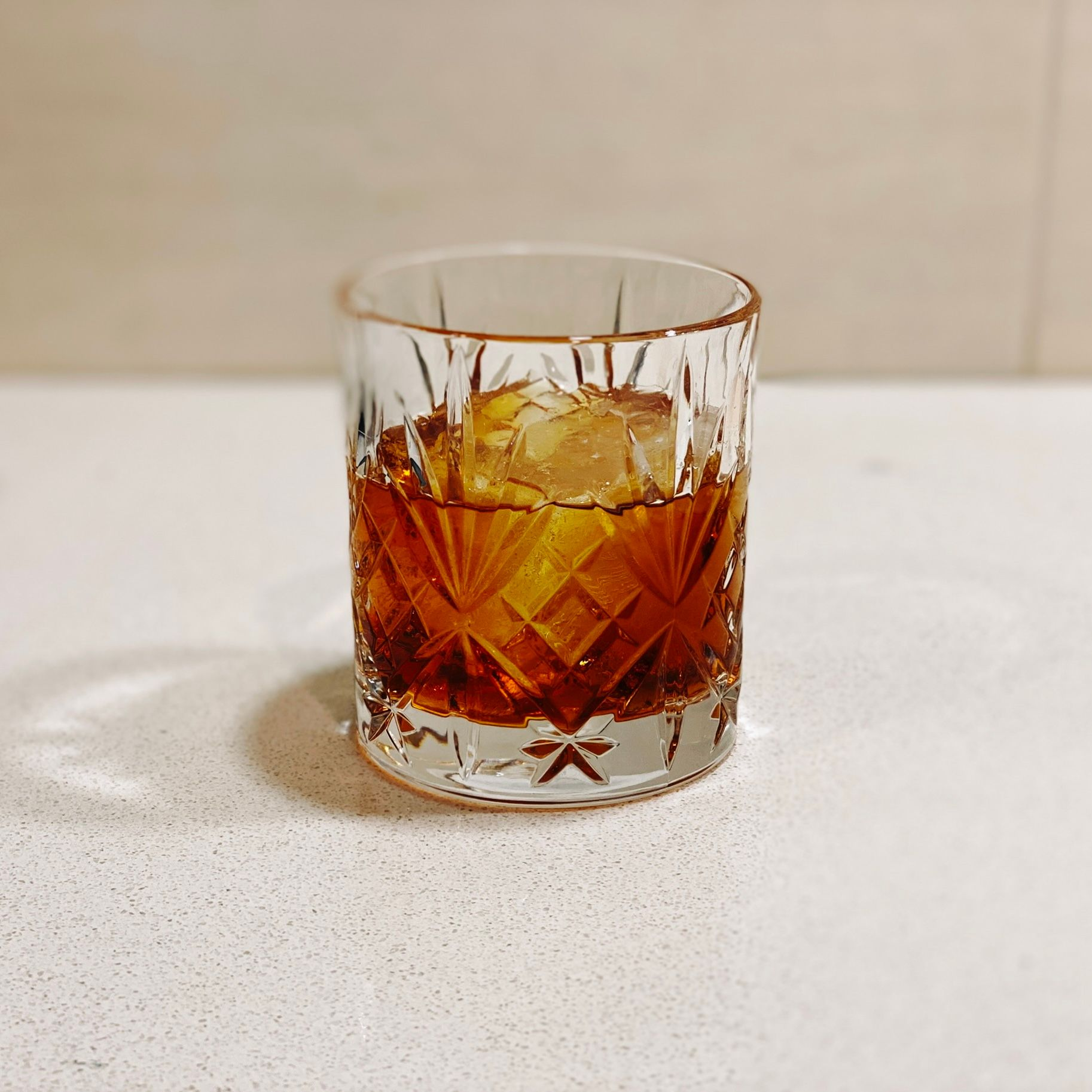 A photo of a small fancy glass with rum in it and a single big ice cube.