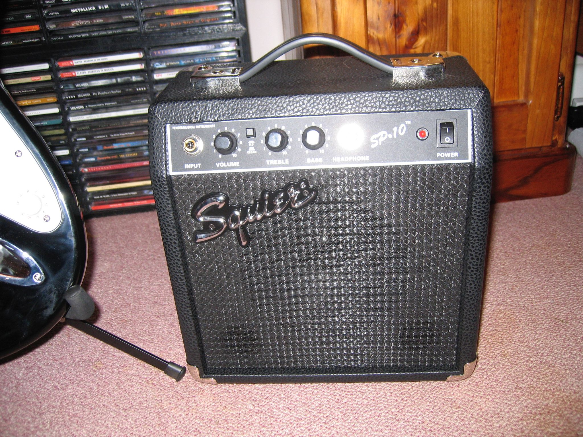 A closeup of a black electric amp sitting on the floor.