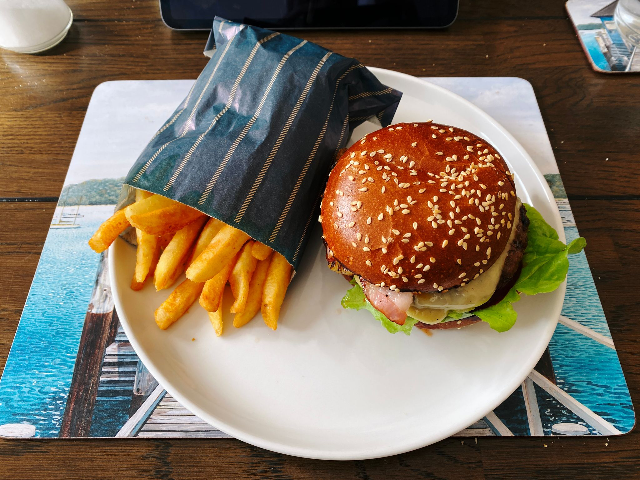 A photo of a burger on a seeded bun with a bag of hot chips next to it, sitting on a plate.
