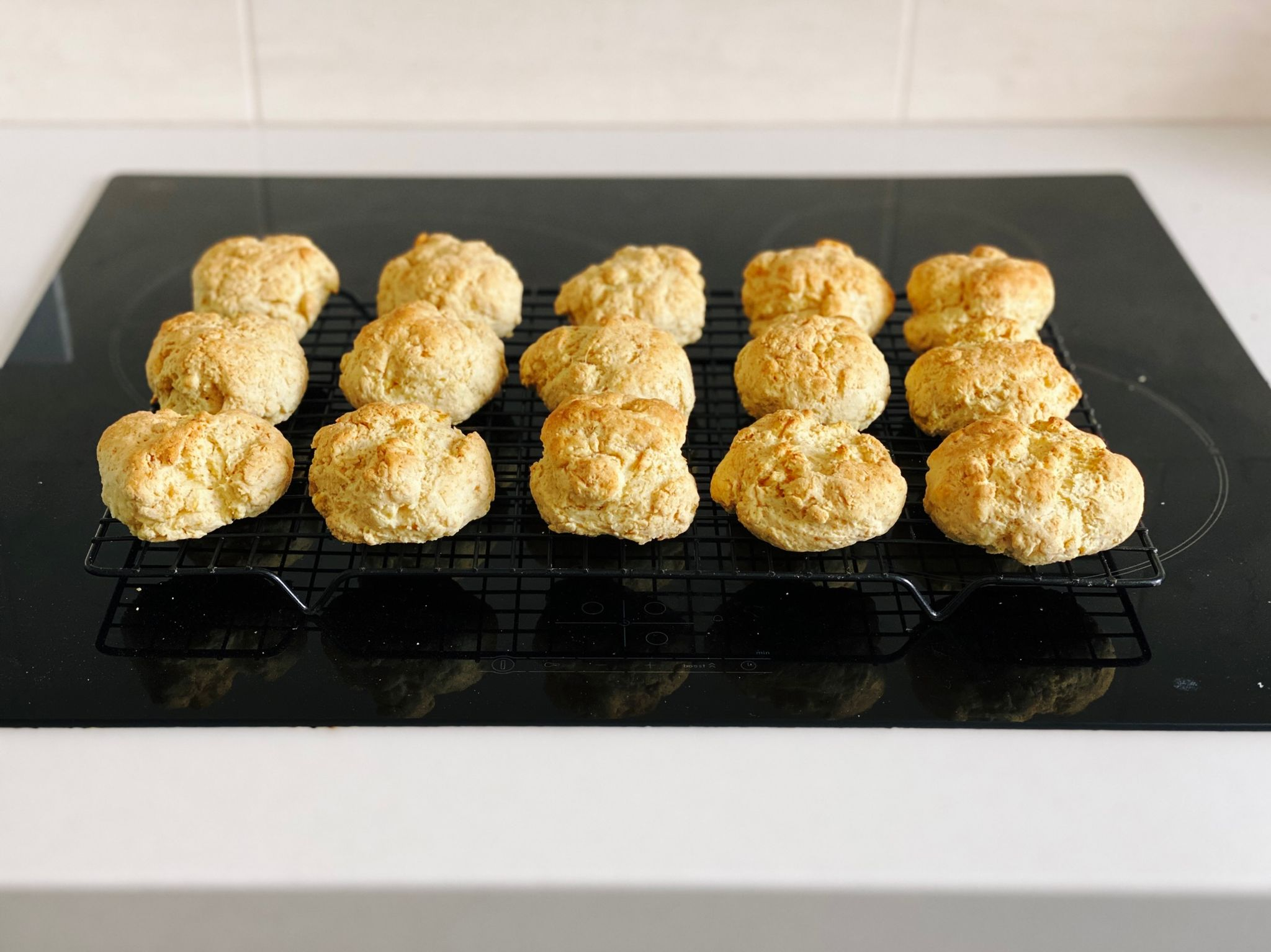 A photo of a bunch of golden-brown cut rounds (basically savoury scones) sitting on a cooling rack.