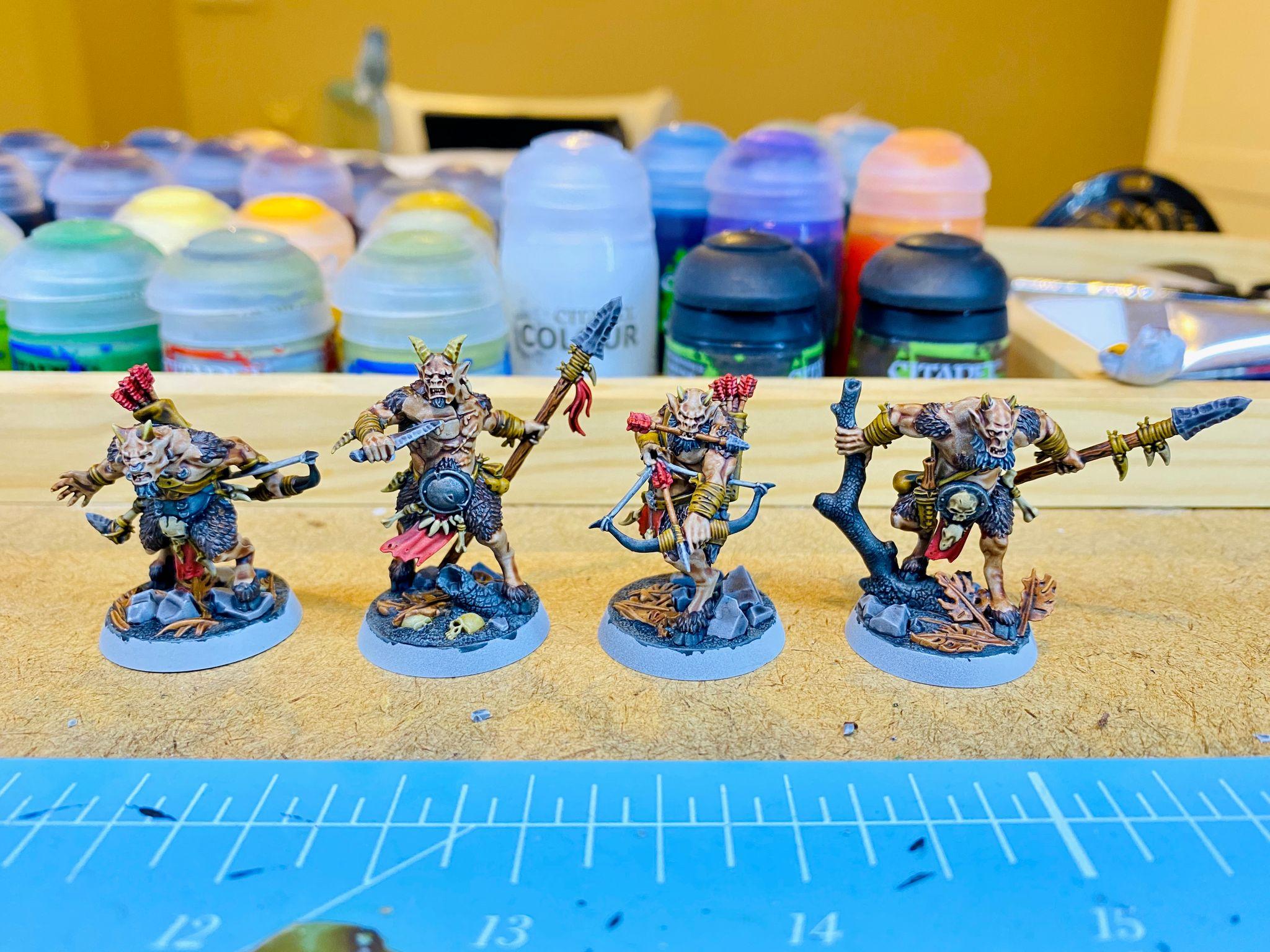 A photo of four goatmen miniatures from Games Workshop's Warhammer Underworlds: Beastgrave brandishing weapons.