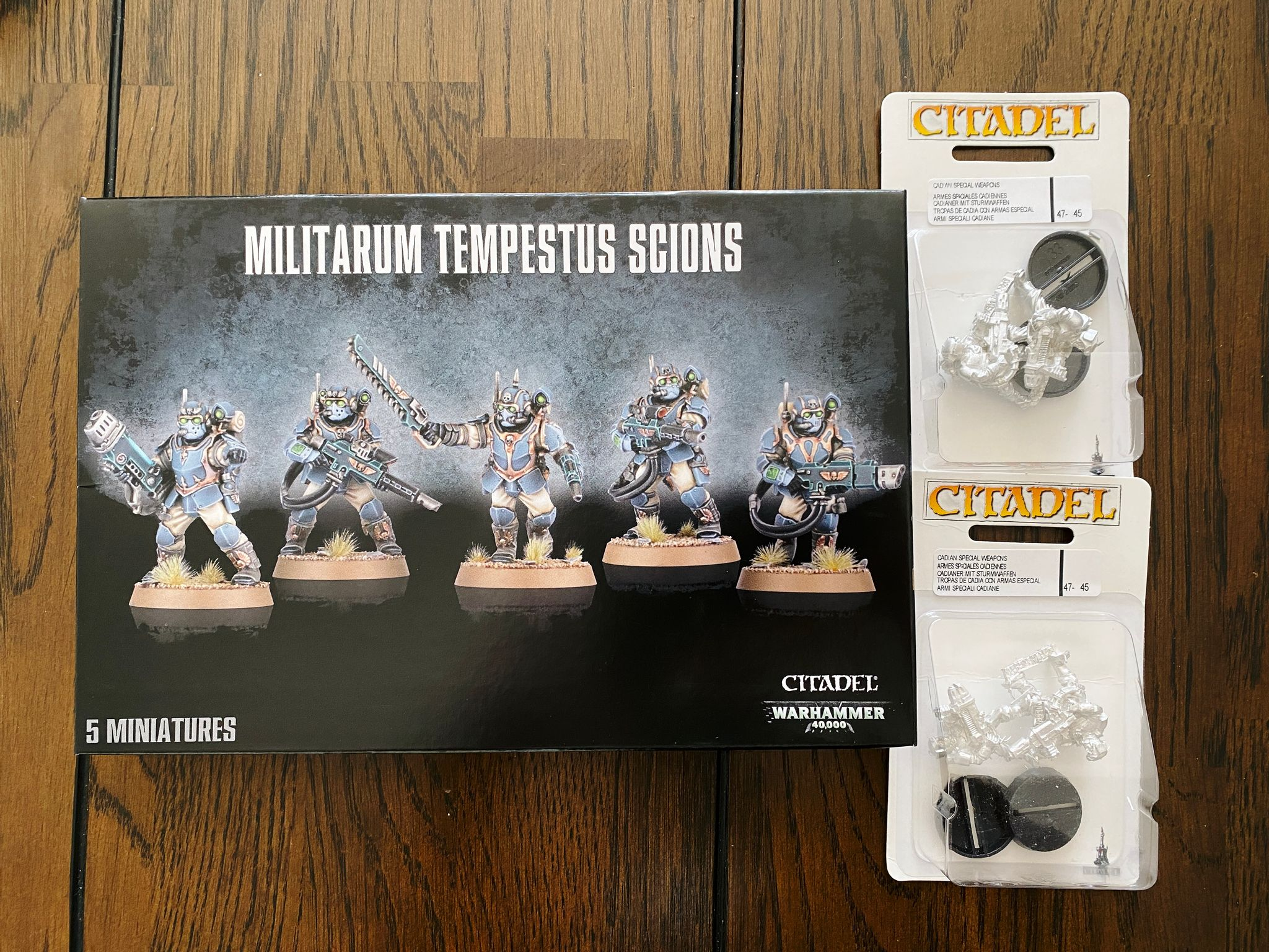 A photo of a box of five Warhammer 40,000 Astra Militarum Tempestus Scions (futuristic-looking armoured dudes with guns), and two packs of regular guardsmen with a plasma gun and a melts gun in each.
