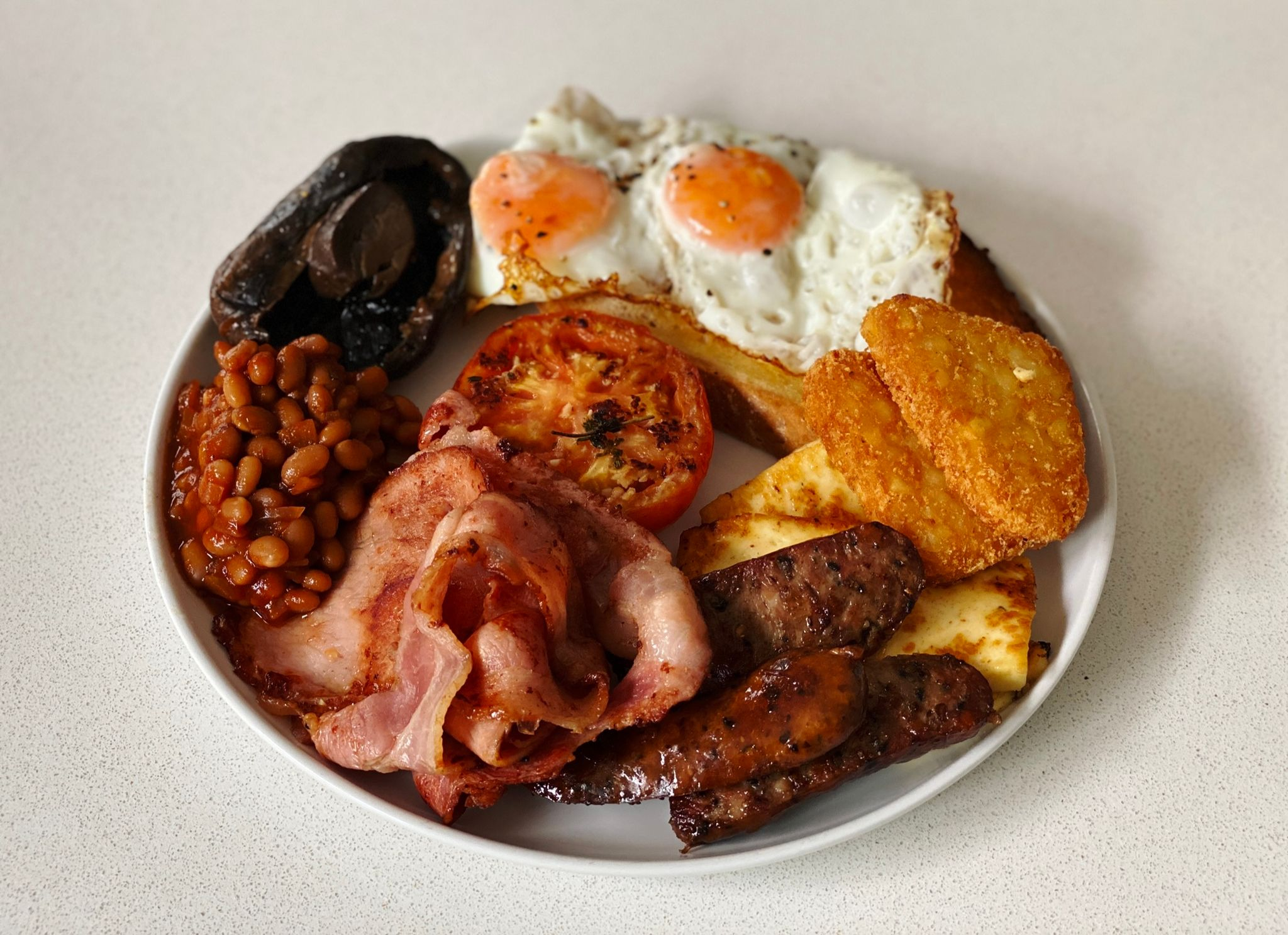 A photo of a not-insignificantly-sized dinner plate that's ENTIRELY covered with food: two eggs on a large piece of sourdough, bacon, mushroom, tomato, haloumi, hashbrowns, sausages, and baked beans.