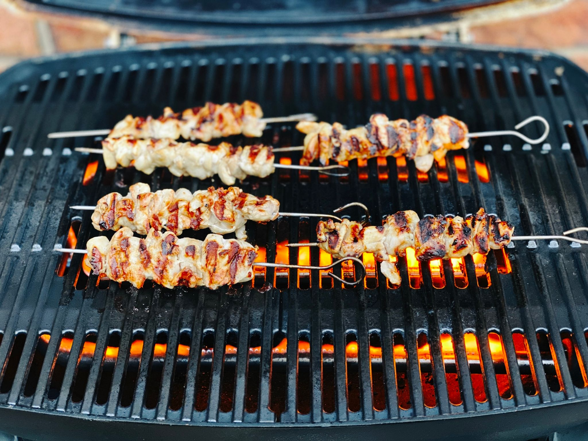 A photo of six chicken skewers being cooked on the barbecue. They've already been flipped over so the top side of them is nice and brown and they look delicious. Underneath the barbecue, the flames are quite orange.