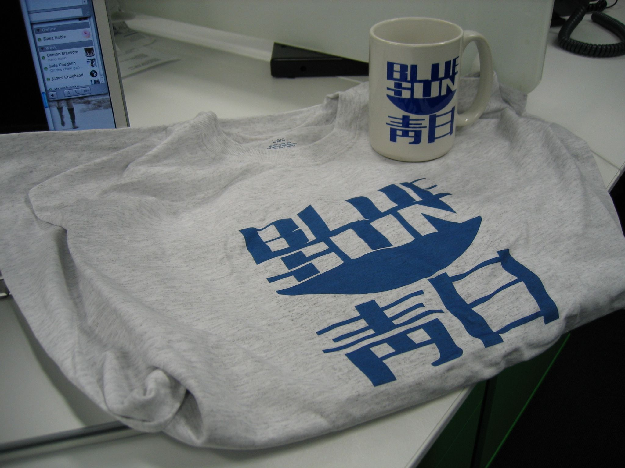 "A photo of a light grey t-shirt and a white mug, both with the ""Blue Sun"" logo and Chinese writing from the TV show ""Firefly""."