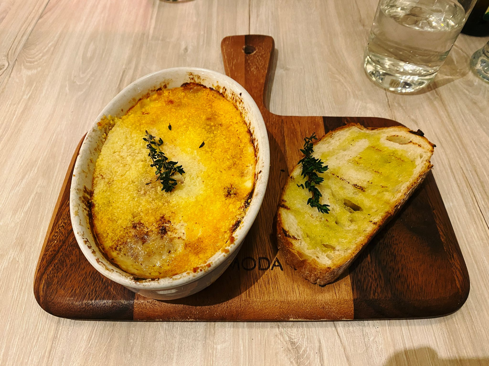 A photo of moussaka in a ceramic dish with a slice of sourdough next to it.