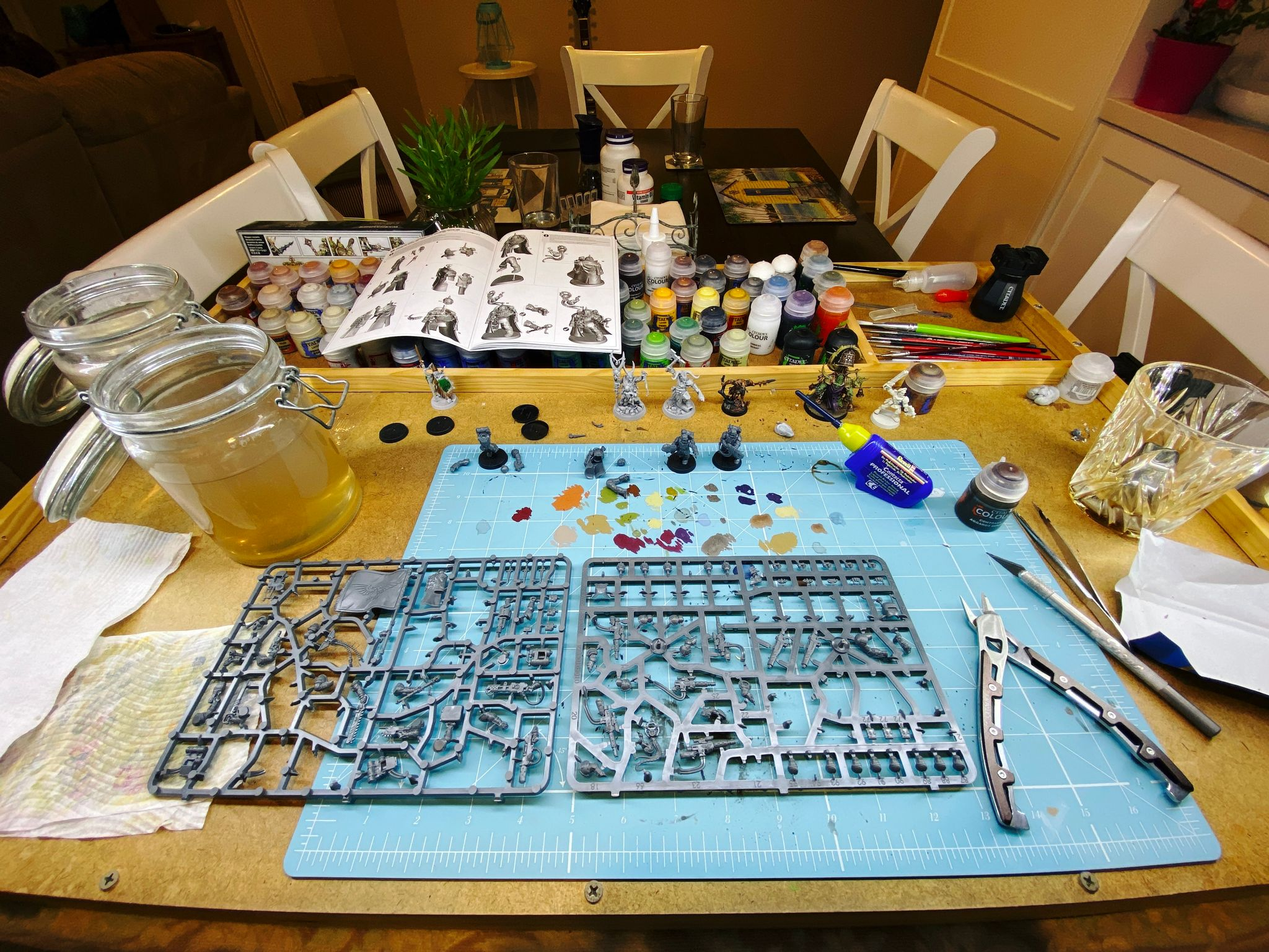 A photo of my painting table with several miniatures in various states of assembly, and two sprues with even more bits still on them, plus an empty glass that had Galliano Ristretto in it.