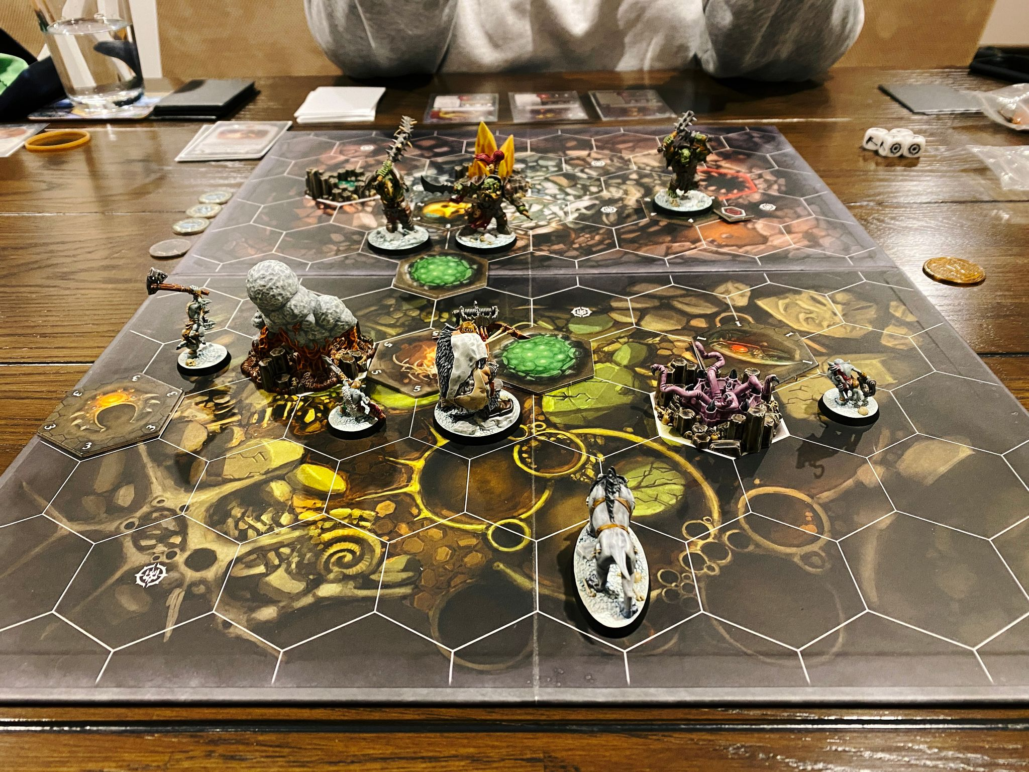 A photo of a Warhammer Underworlds board, with tiled hexes on it. Hrothgorn's Mantrappers are at the front, consisting of a large ogre with a huge crossbow and wearing lots of animal skins, a sabretooth tiger, and three gnoblars (goblins). Facing them are Morgok's Krushas, three heavily armed and armoured orruks (orks).