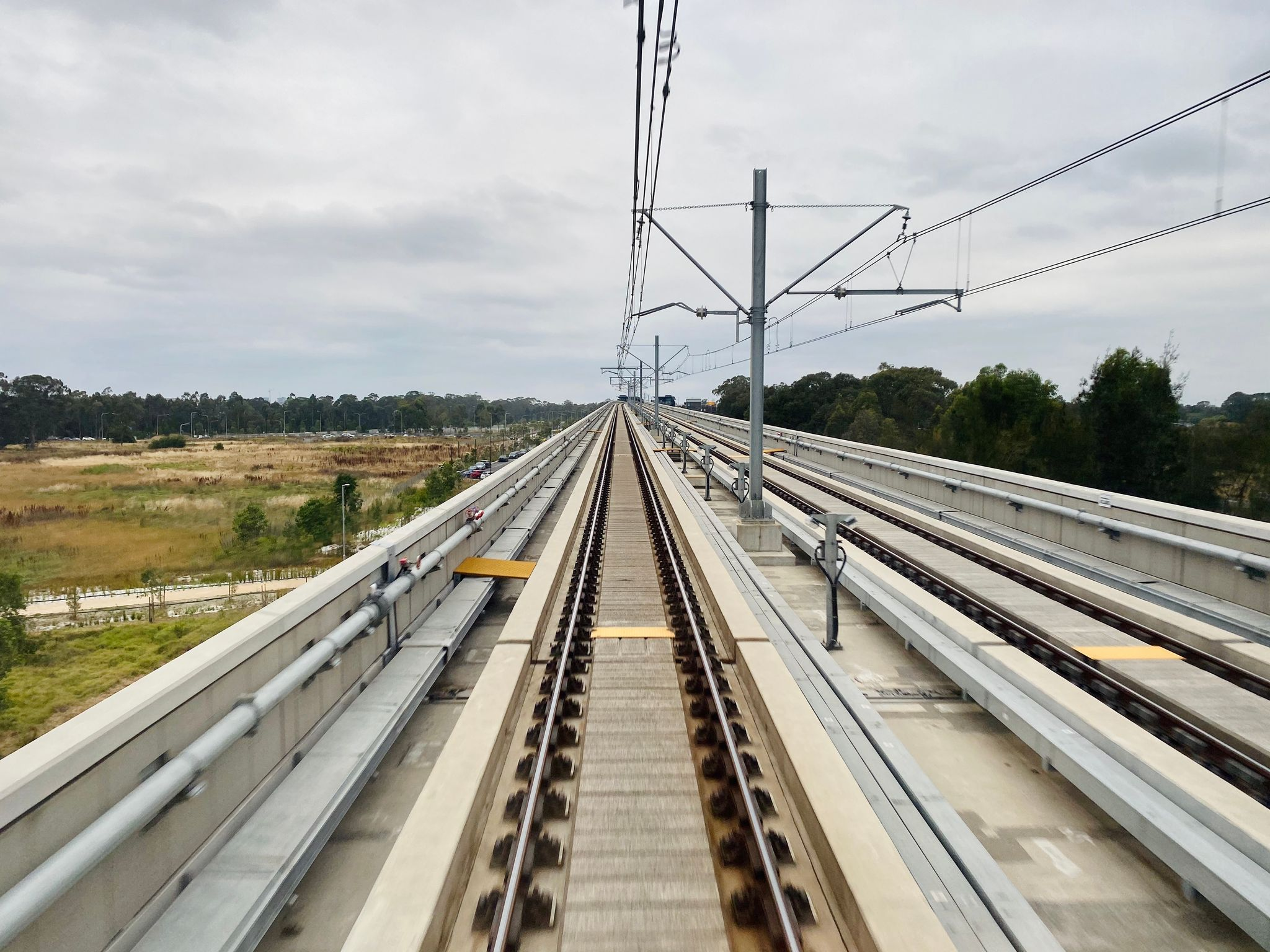 A photo from the front of a train looking out at the tracks going off into the distance. It's an above-ground part of the route and the sky above is grey and cloudy.