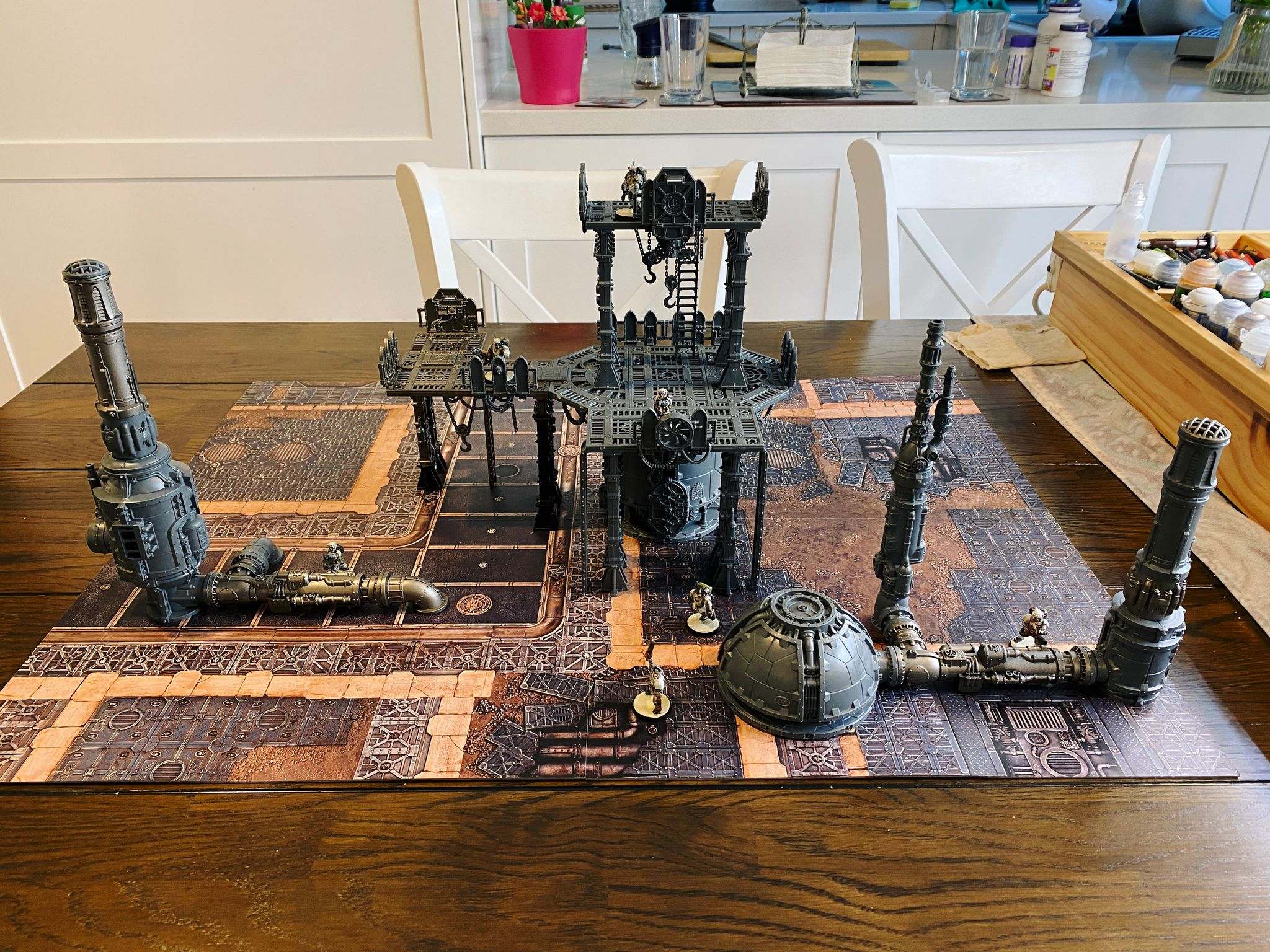 A photo of a Warhammer 40,000 Kill Team board with three pieces of bit chunky industrial-looking terrain on it. Two have horizontal pipes going into chimney stacks, and the centrepiece is a massive two-storey thing with a wide platform on the first level and a smaller one in the middle on the second.